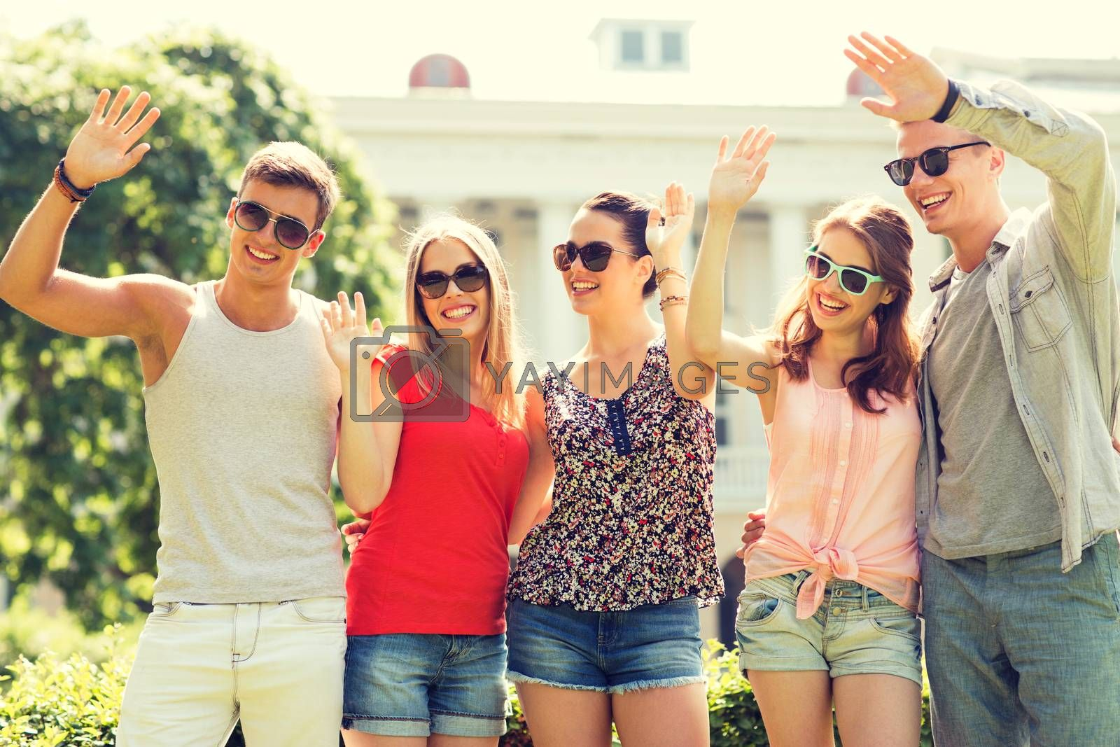 friendship, leisure, summer, gesture and people concept - group of smiling friends waving hands outdoors