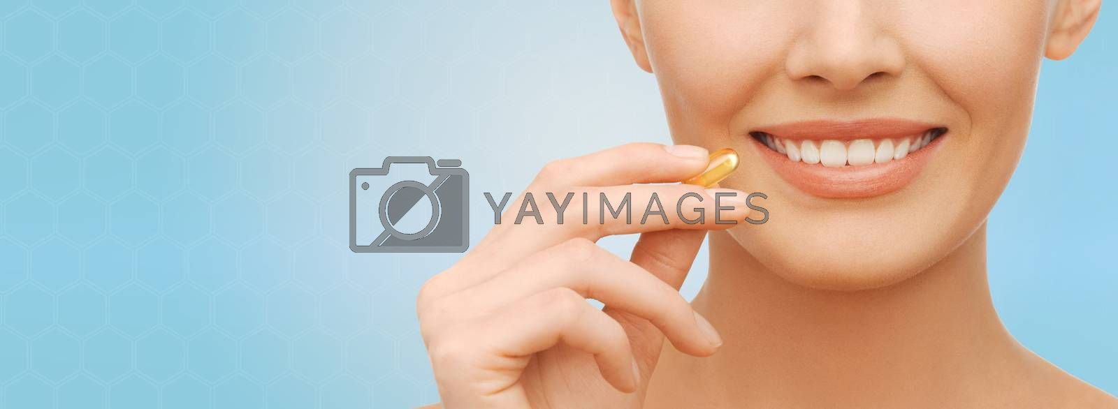 healthcare, people and beauty concept - beautiful woman face and hand holding omega 3 vitamins capsule over blue background