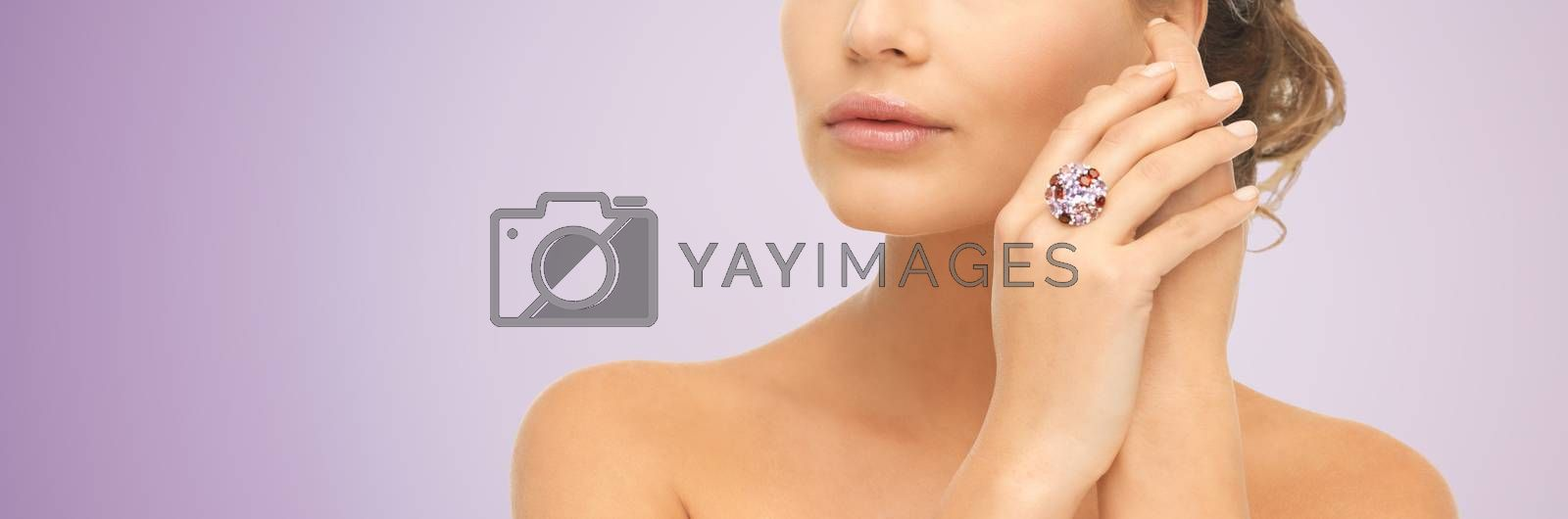 beauty, jewelry, people and accessories concept - close up of woman with cocktail ring on hand over violet background