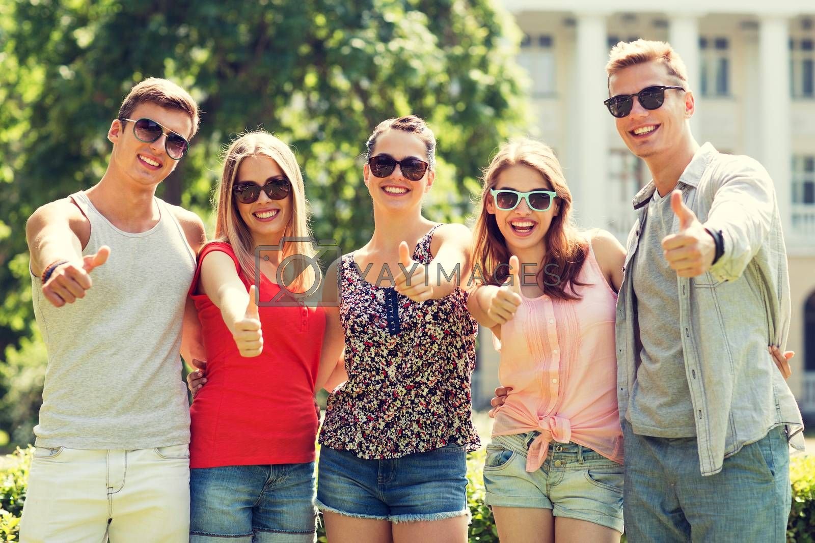 friendship, leisure, summer, gesture and people concept - group of smiling friends showing thumbs up outdoors