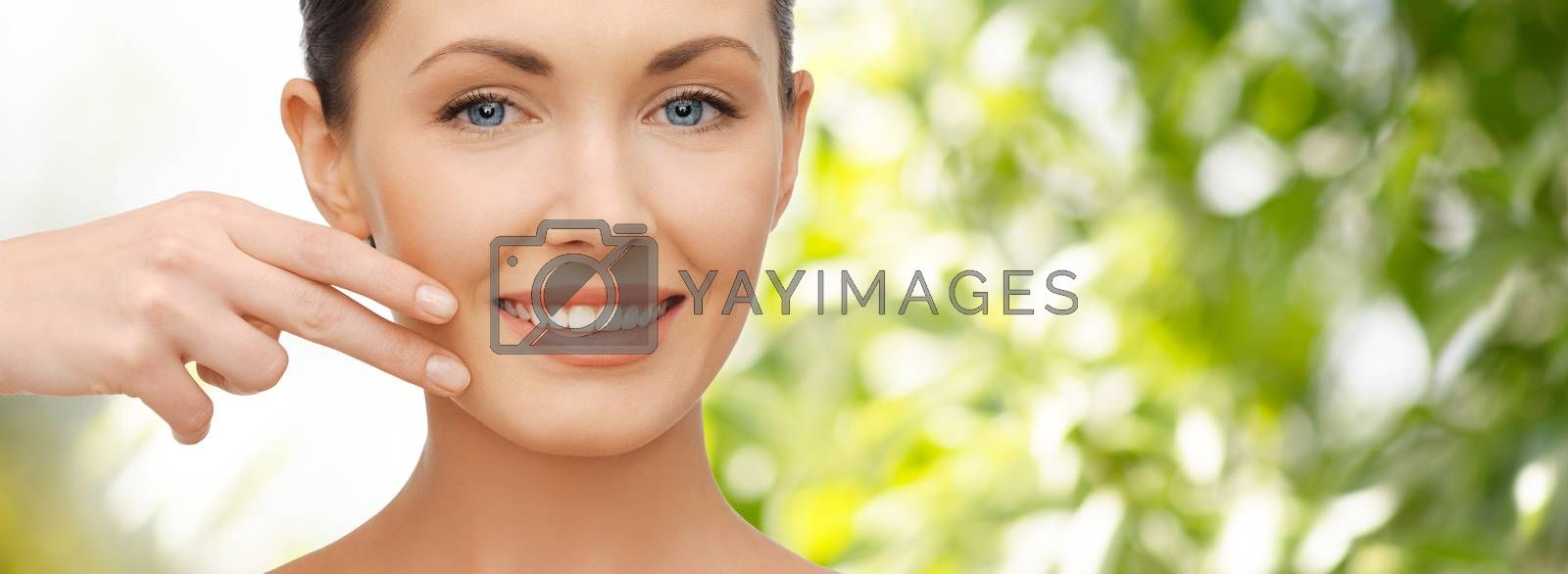 healthcare, people and beauty concept - beautiful woman touching her face skin over green natural background