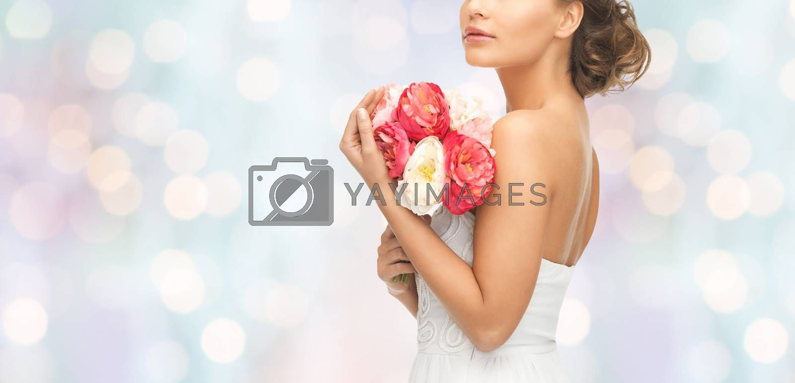 wedding, holidays, people and celebration concept- bride or woman with bouquet of flowers over blue holidays lights background