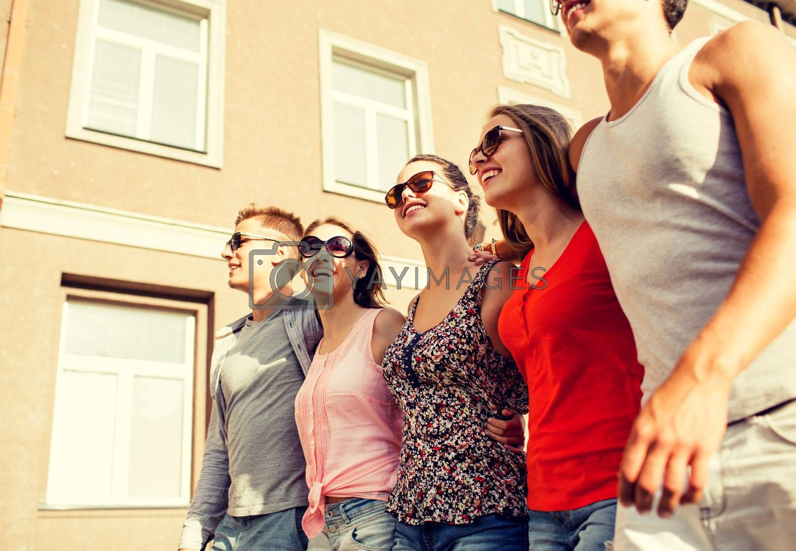 friendship, leisure, summer, gesturer and people concept - group of smiling friends walking in city