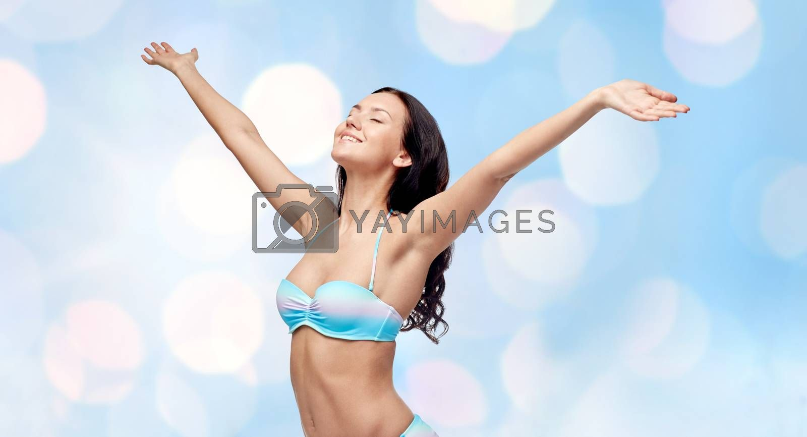 people, summer, happiness and beach concept - happy young woman in bikini swimsuit with raised hands and closed eyes over blue holidays lights background