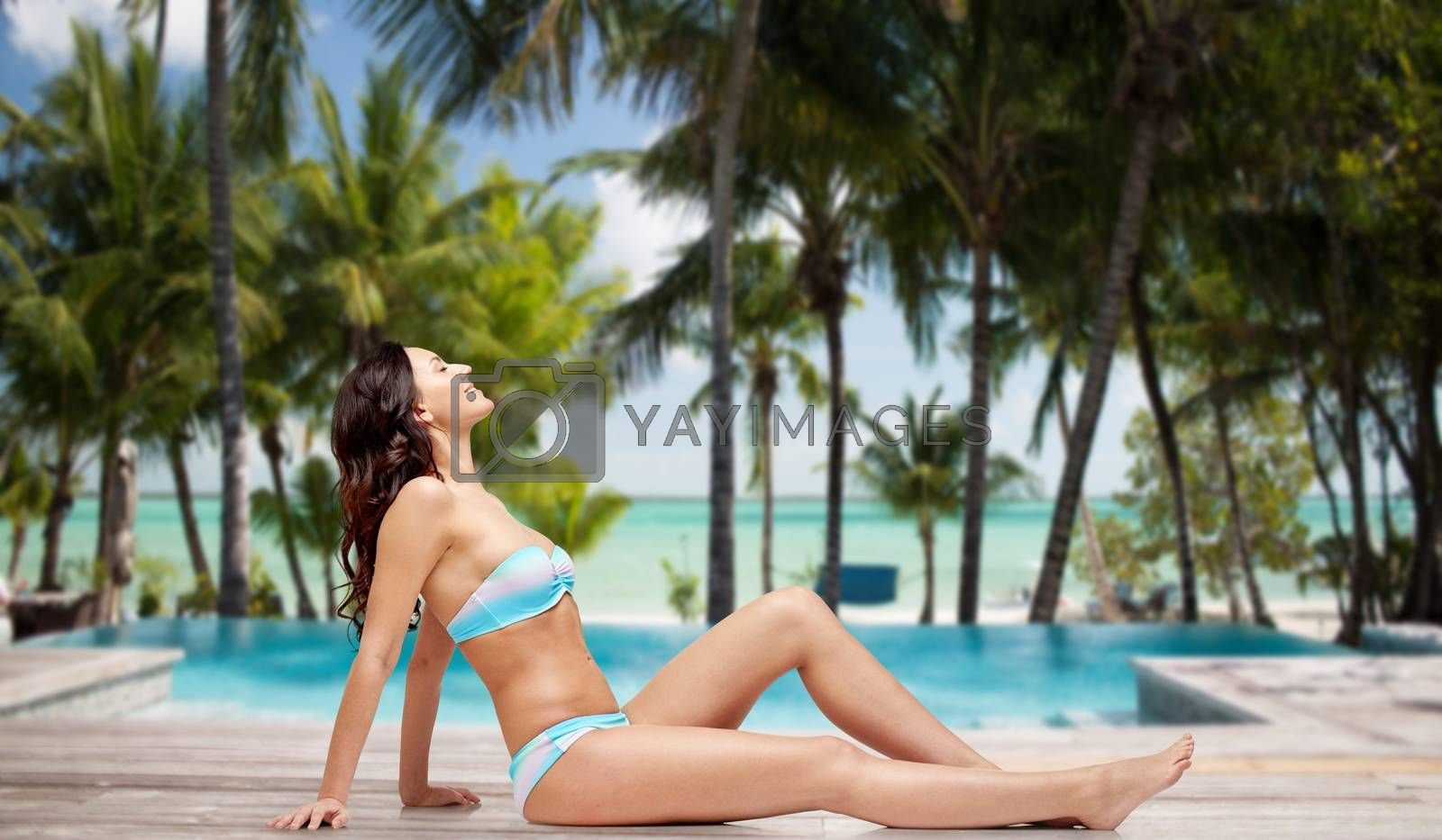 people, fashion, swimwear, summer and travel concept - happy young woman tanning in bikini swimsuit over tropical beach with swimming pool background