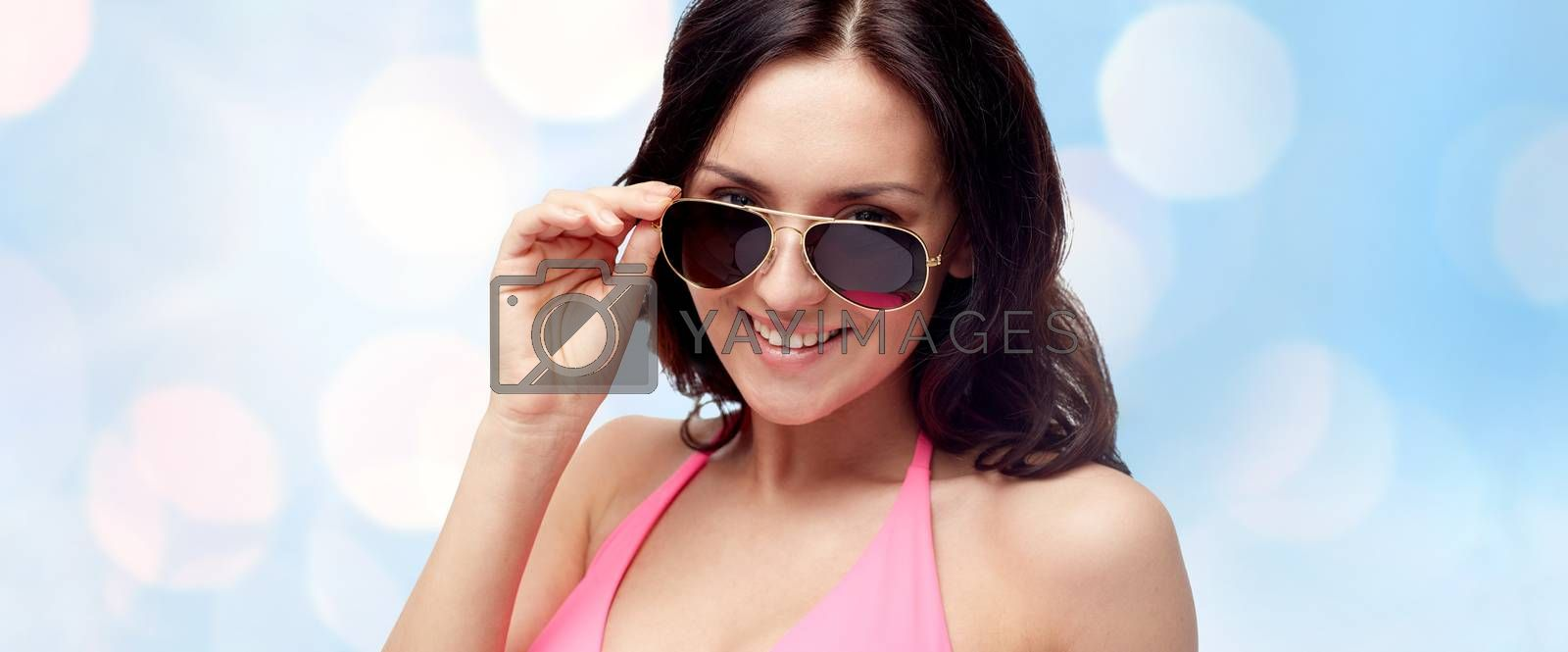people, fashion, swimwear, summer and beach concept - happy young woman in sunglasses and pink swimsuit looking at you over blue holidays lights background