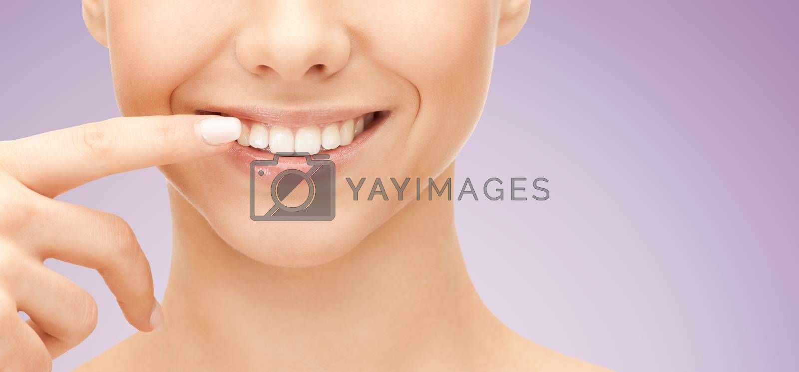 dental health, beauty, hygiene and people concept - close up of smiling woman face pointing to teeth over violet background
