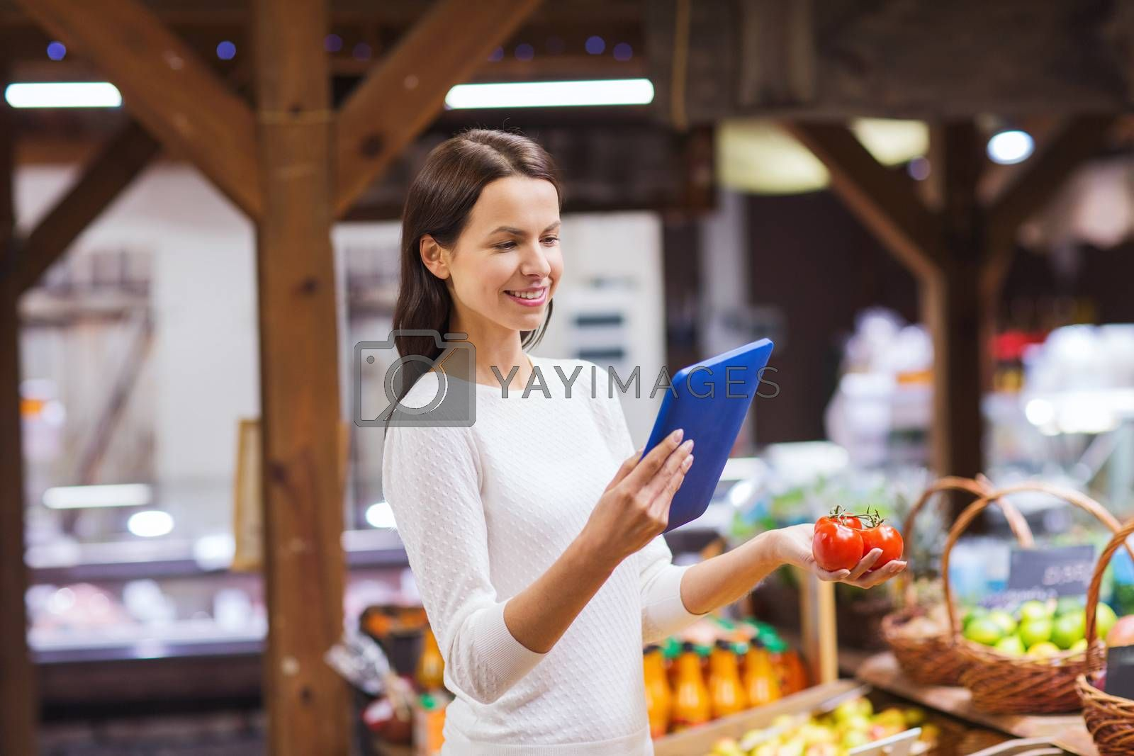 sale, shopping, consumerism and people concept - happy young woman with tomatoes and tablet pc computer in market