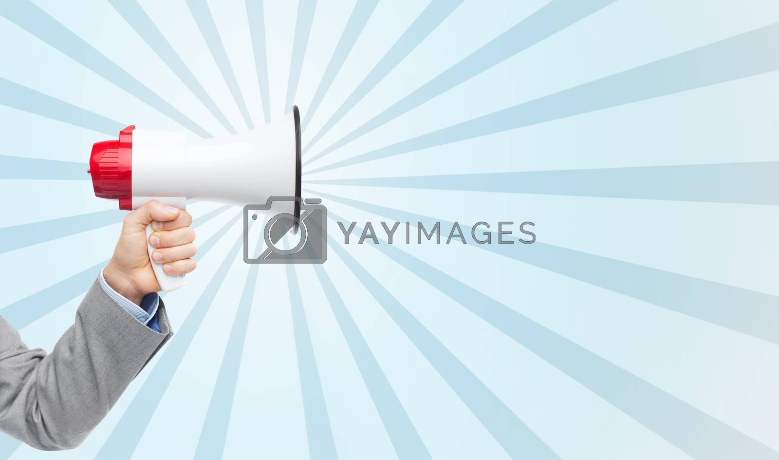 business, people and public announcement concept - close up of male hand in suit with megaphone over blue burst rays background