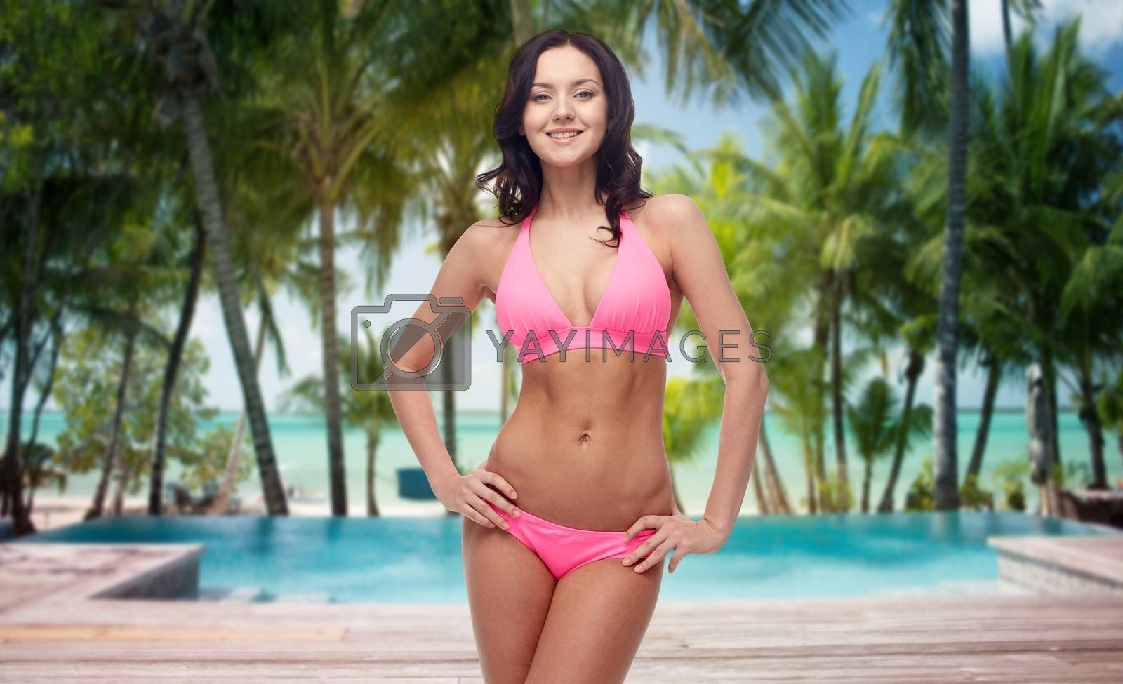people, fashion, swimwear, summer and travel concept - happy young woman posing in pink bikini swimsuit over tropical beach with swimming pool background