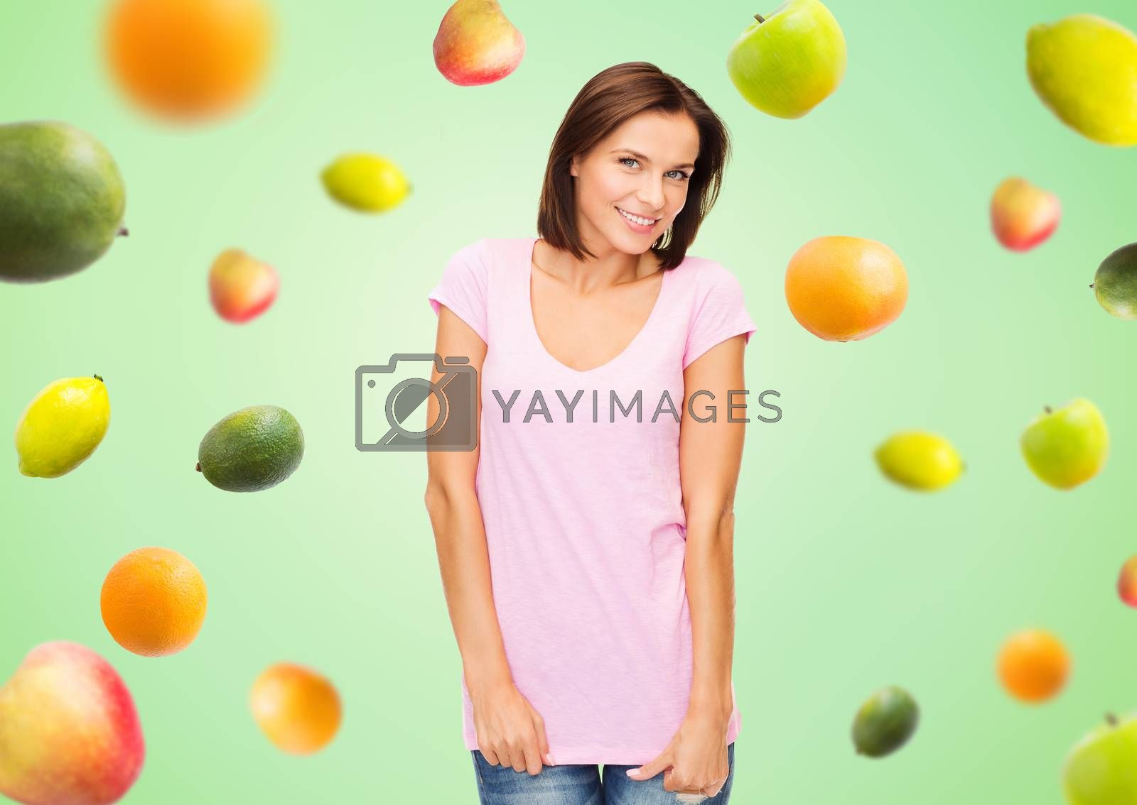 people, advertisement, diet, food and healthy eating concept - happy woman in blank pink t-shirt over fruits on green background