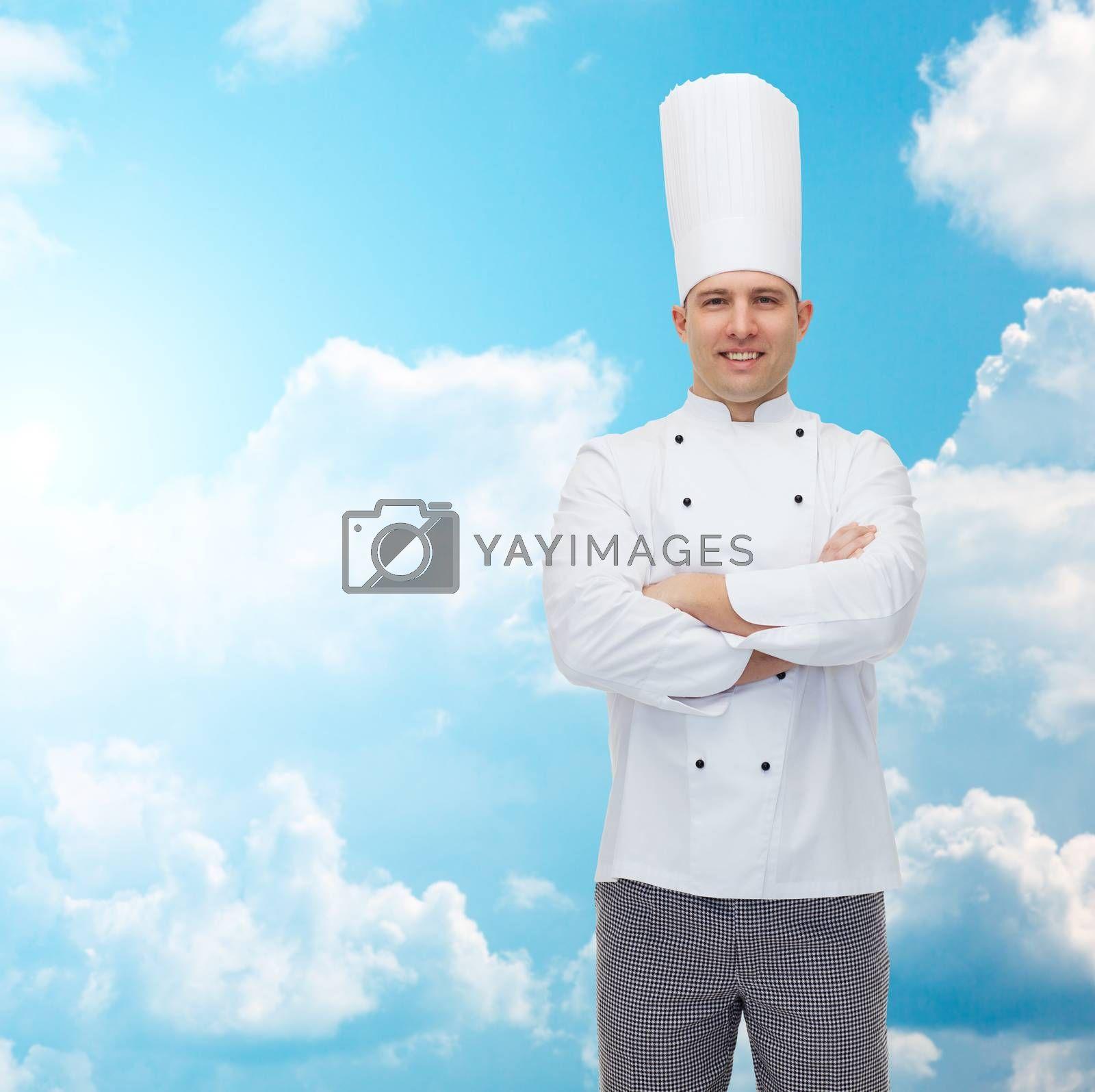 cooking, profession and people concept - happy male chef cook with crossed hands over blue sky with clouds background