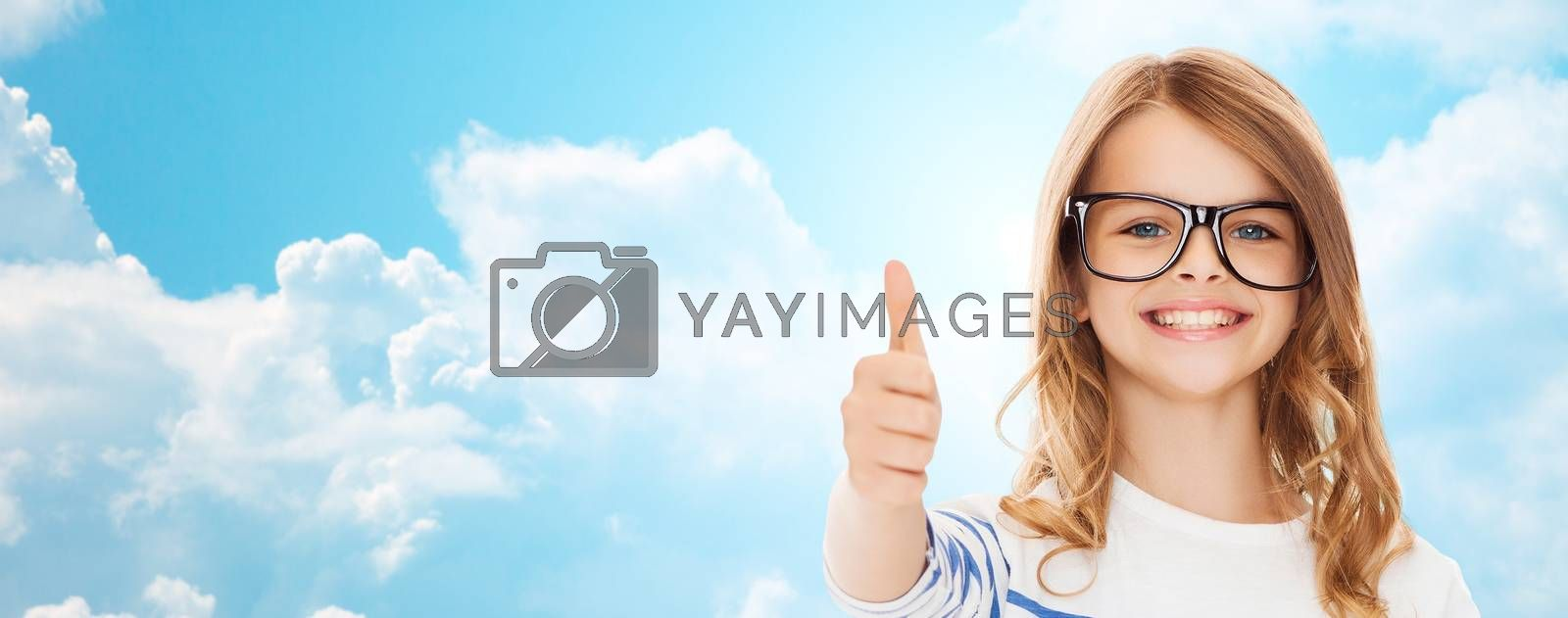 education, school, childhood, people and vision concept - smiling cute little girl with black eyeglasses showing thumbs up gesture over blue sky and white clouds background