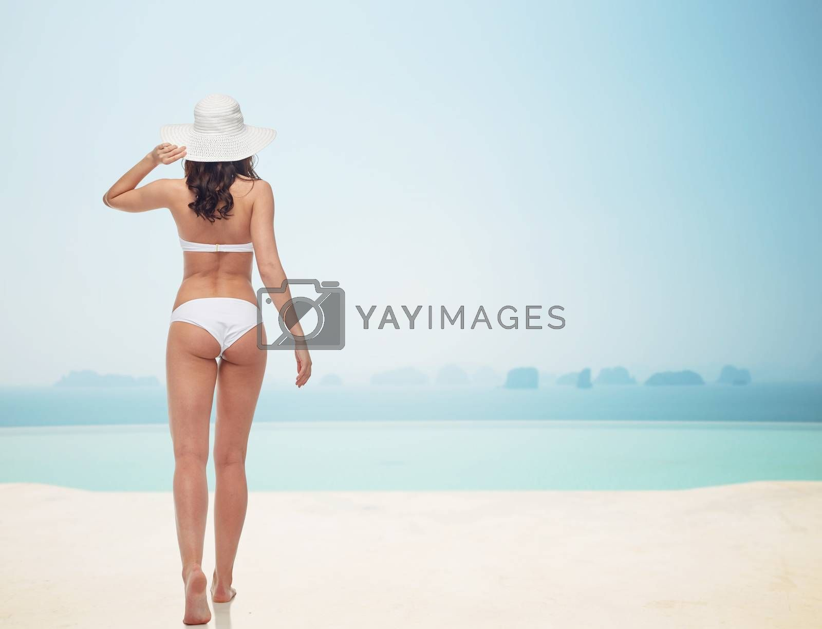 people, fashion, swimwear, summer beach and beauty concept - young woman in white bikini swimsuit from back over infinity pool at beach resort