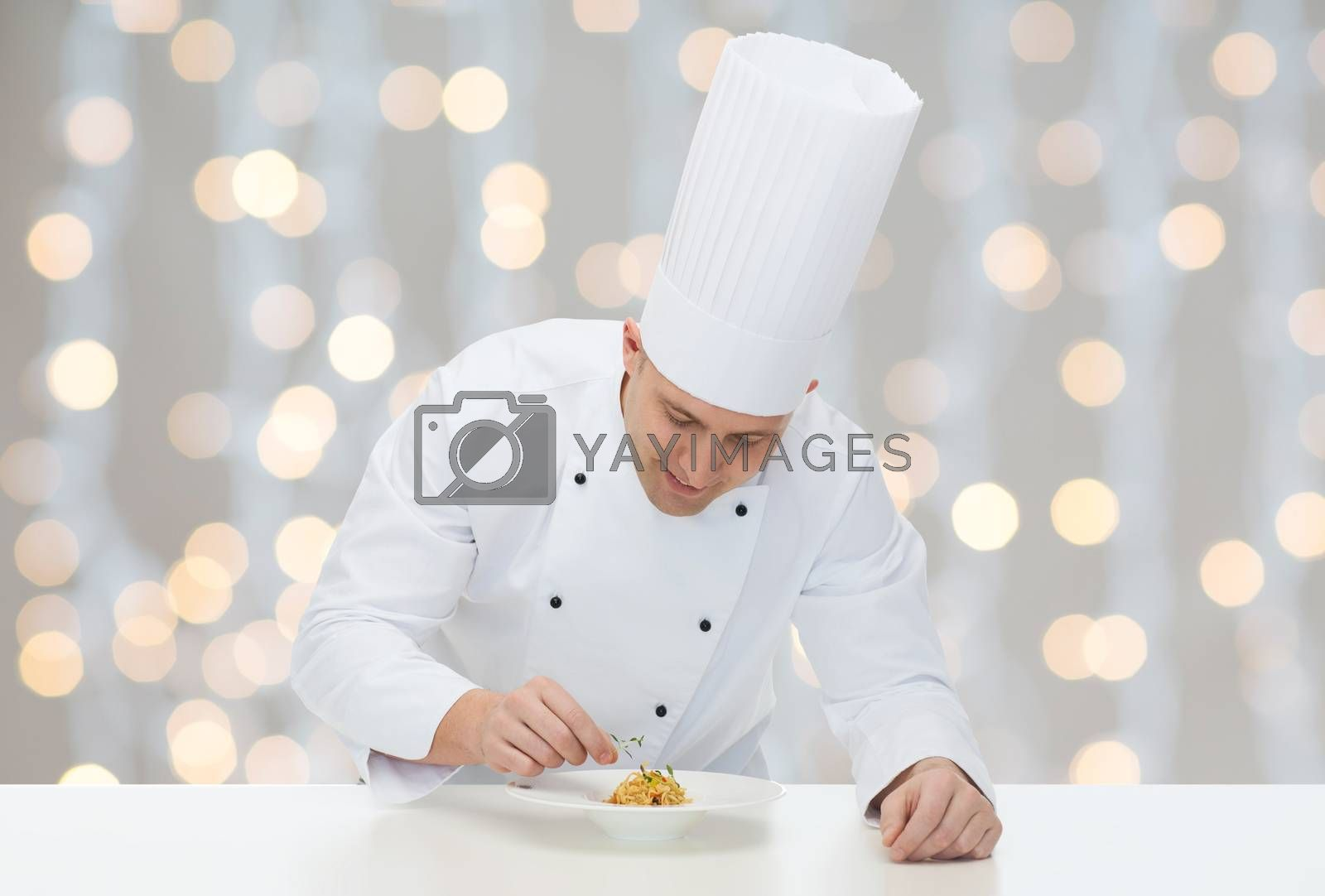 cooking, profession, haute cuisine, food and people concept - happy male chef cook decorating dish over christmas holidays lights background