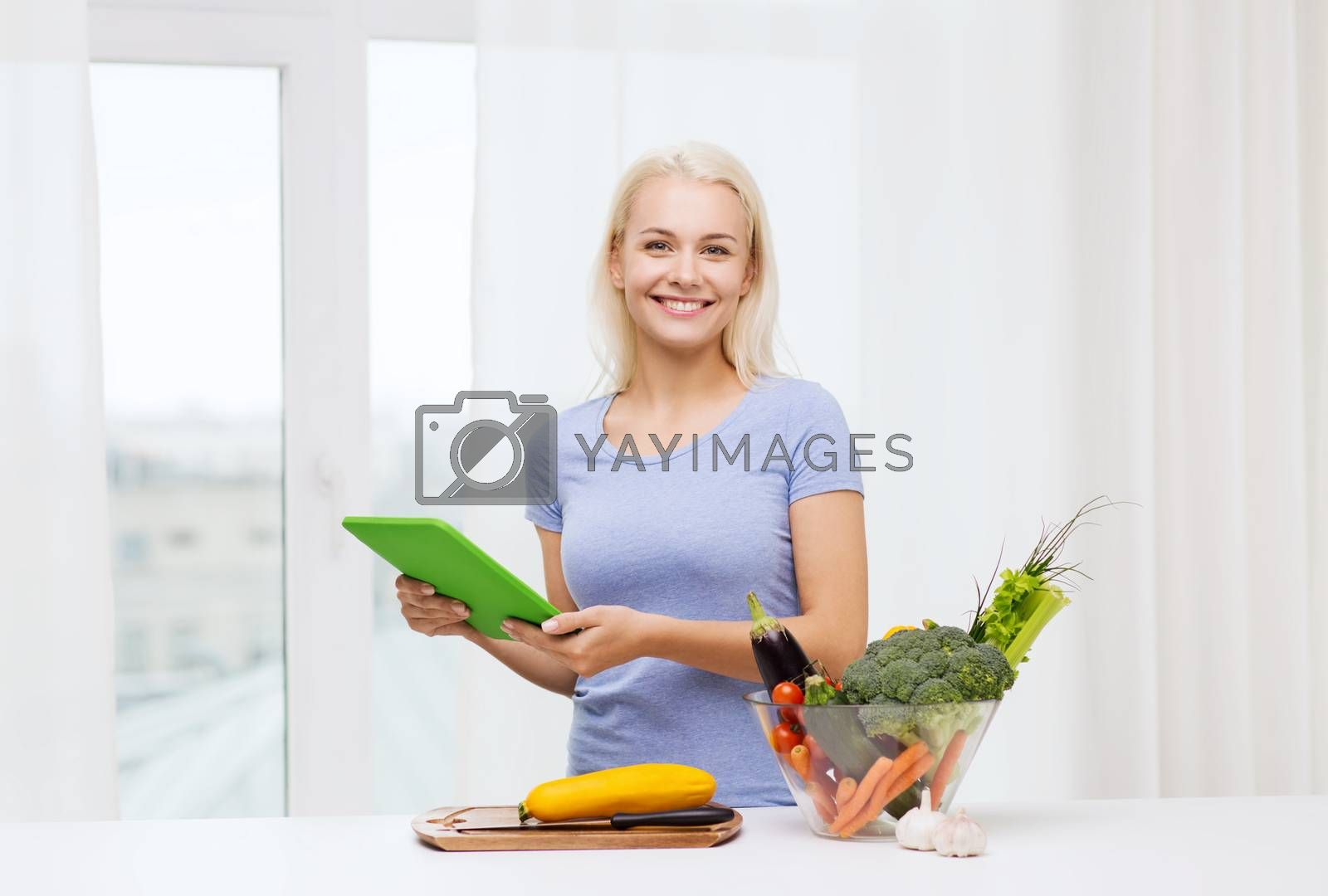 healthy eating, cooking, vegetarian food, technology and people concept - smiling young woman with tablet pc computer and bowl of vegetables at home