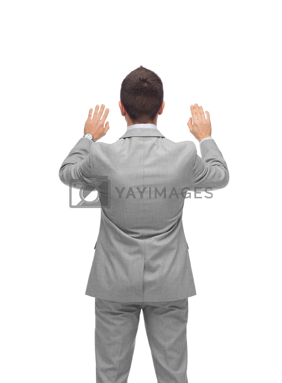 business, people, advertisement and office concept - businessman touching something imaginary from back