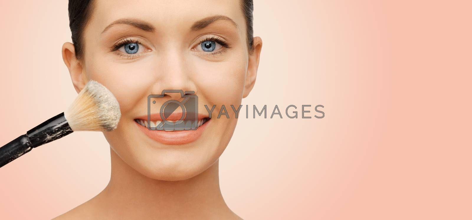 beauty, people and makeup concept - happy woman face applying powder foundation with brush over beige background