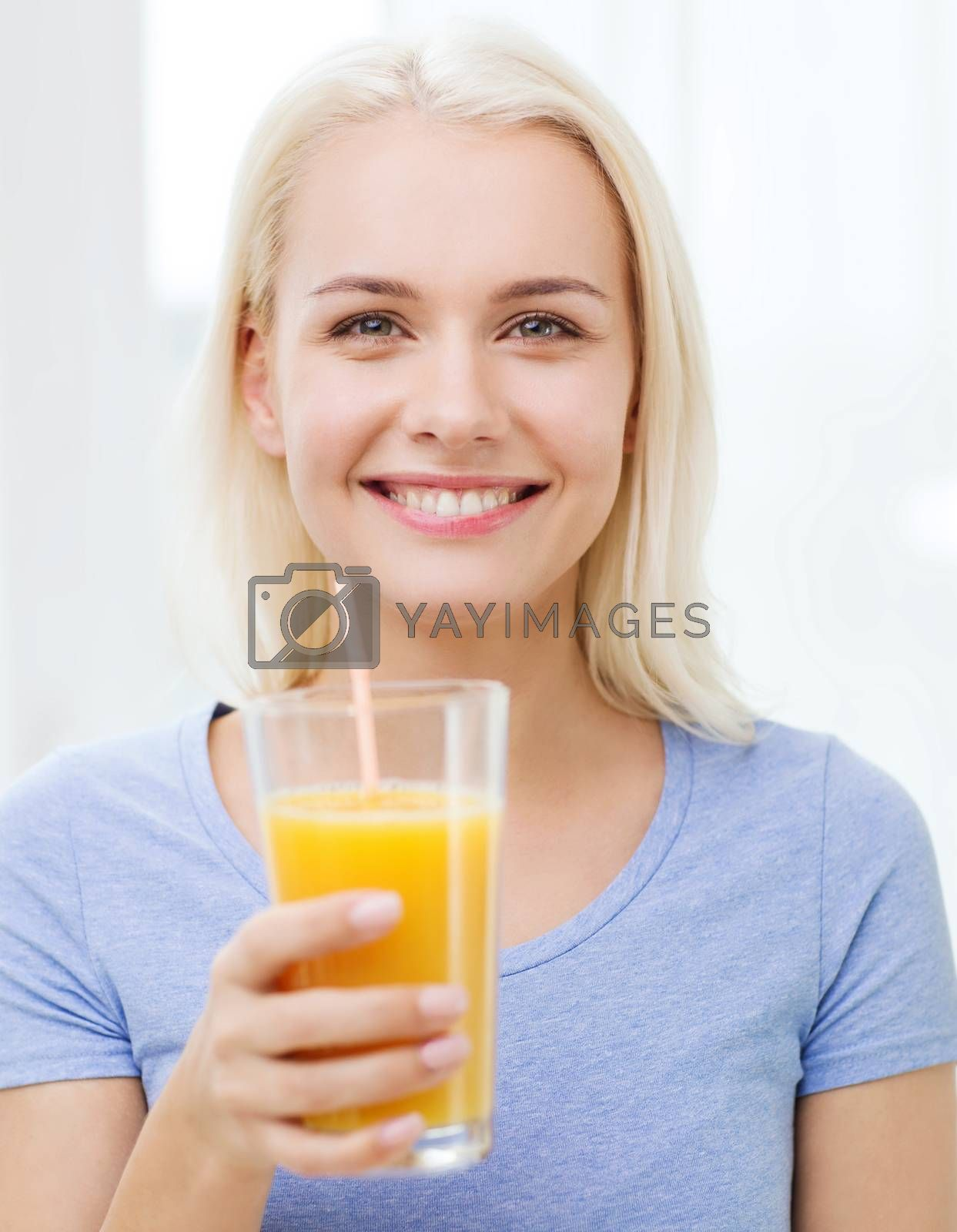 healthy eating, vegetarian food, diet, detox and people concept - smiling woman drinking orange juice or shake from glass at home