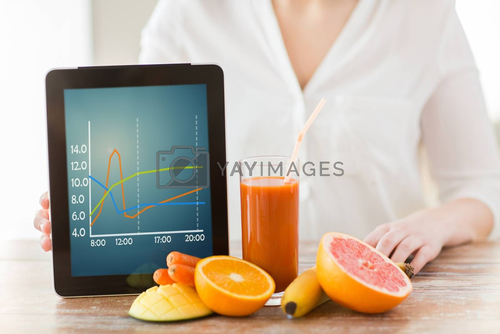 healthy eating, technology, diet and people concept - close up of woman hands holding tablet pc computer with chart, fruits and fresh juice sitting at table