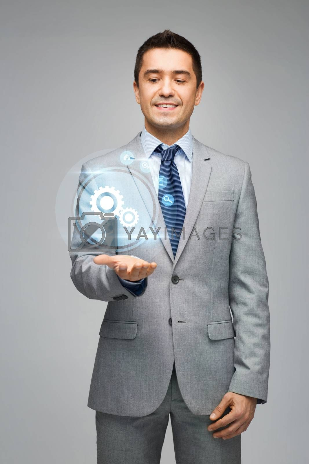 business, people and technology concept - happy businessman in suit showing or holding virtual projection of computer settings on hand palm over gray background