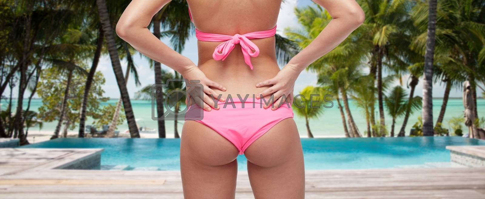people, fashion, swimwear, summer and travel concept - close up of young woman buttocks in pink bikini over tropical beach with swimming pool background