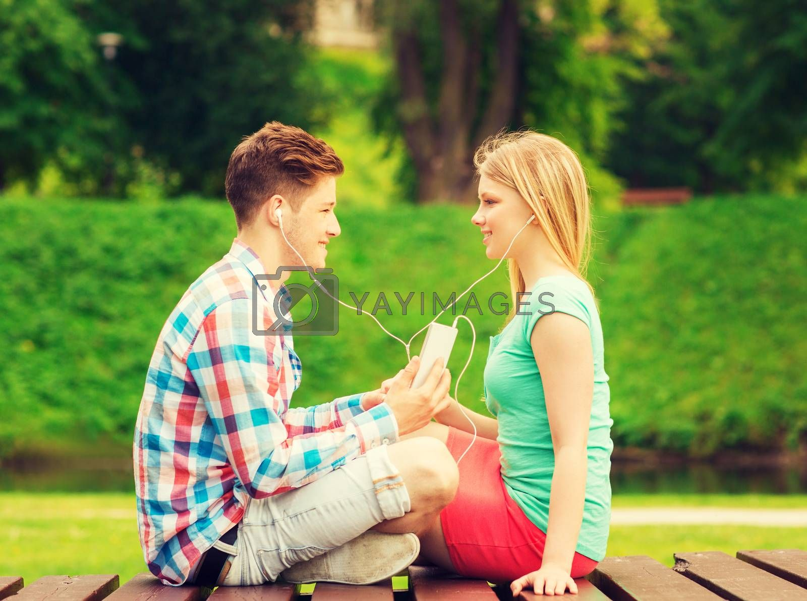 summer, vacation, holidays, technology and friendship concept - smiling couple with smartphone and earphones sitting on bench in park