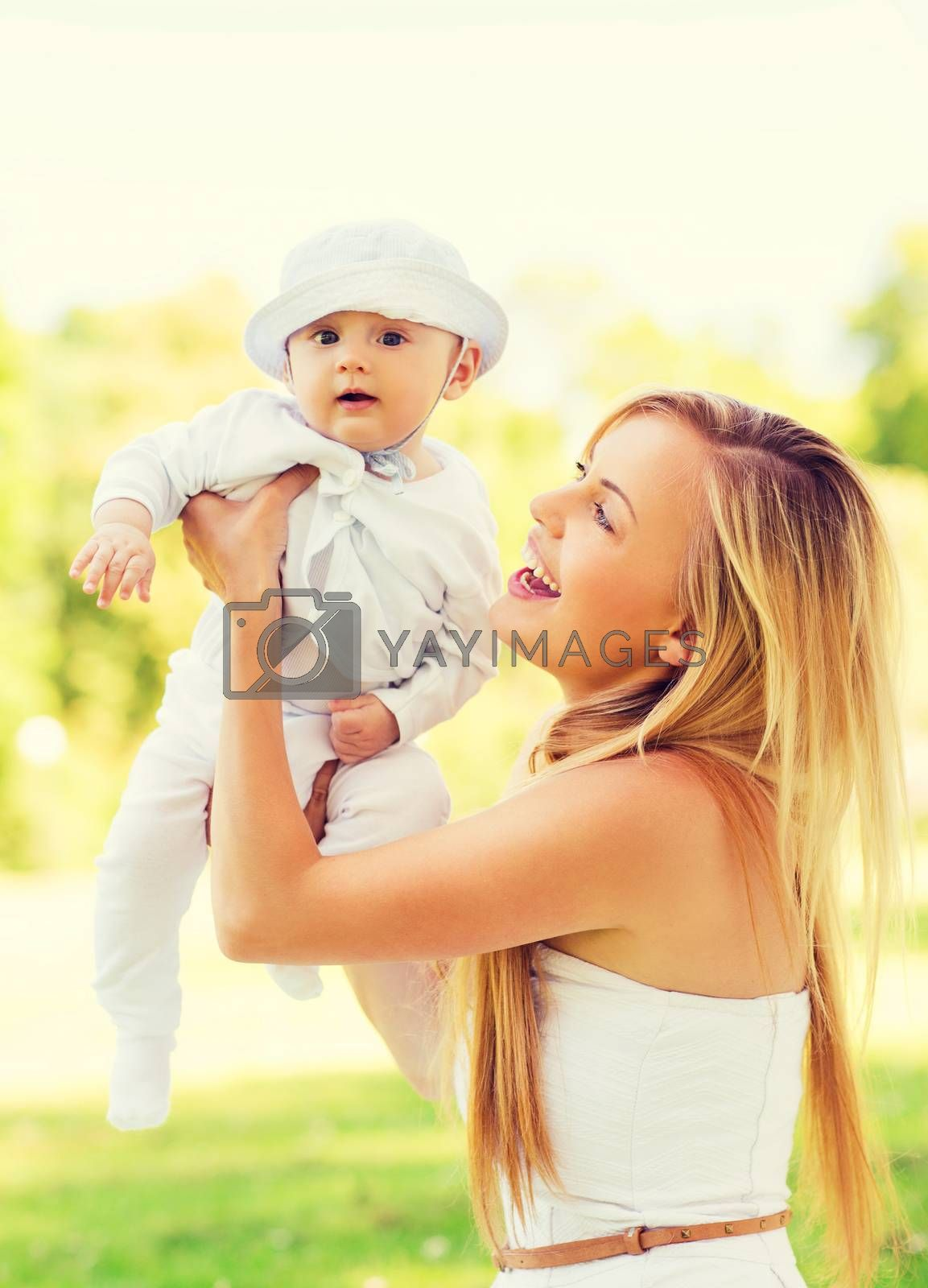 family, child, happiness and motherhood concept - happy mother with little baby sitting on blanket in park