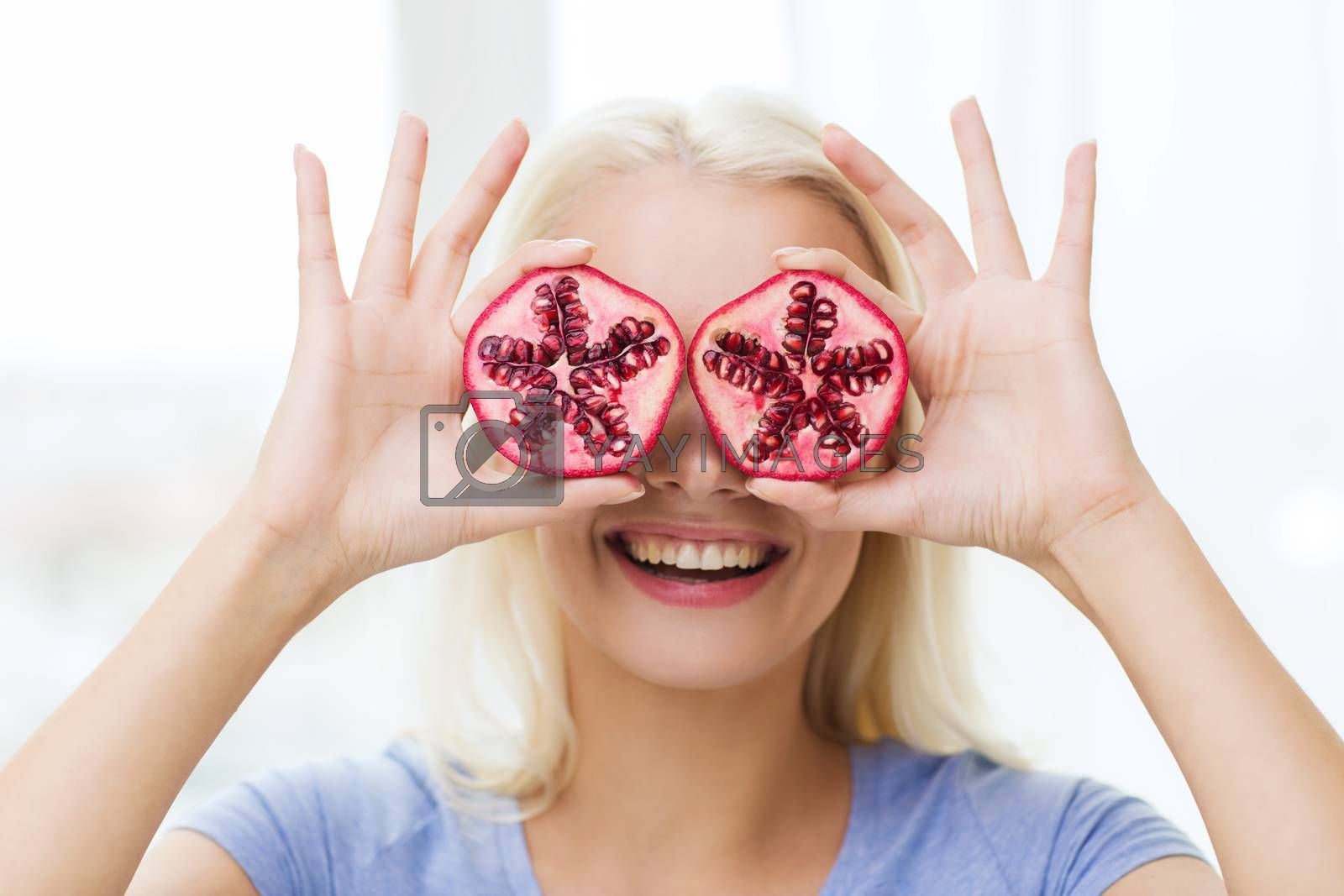 healthy eating, organic food, fruit diet, comic and people concept - happy woman having fun and covering her eyes with pomegranate