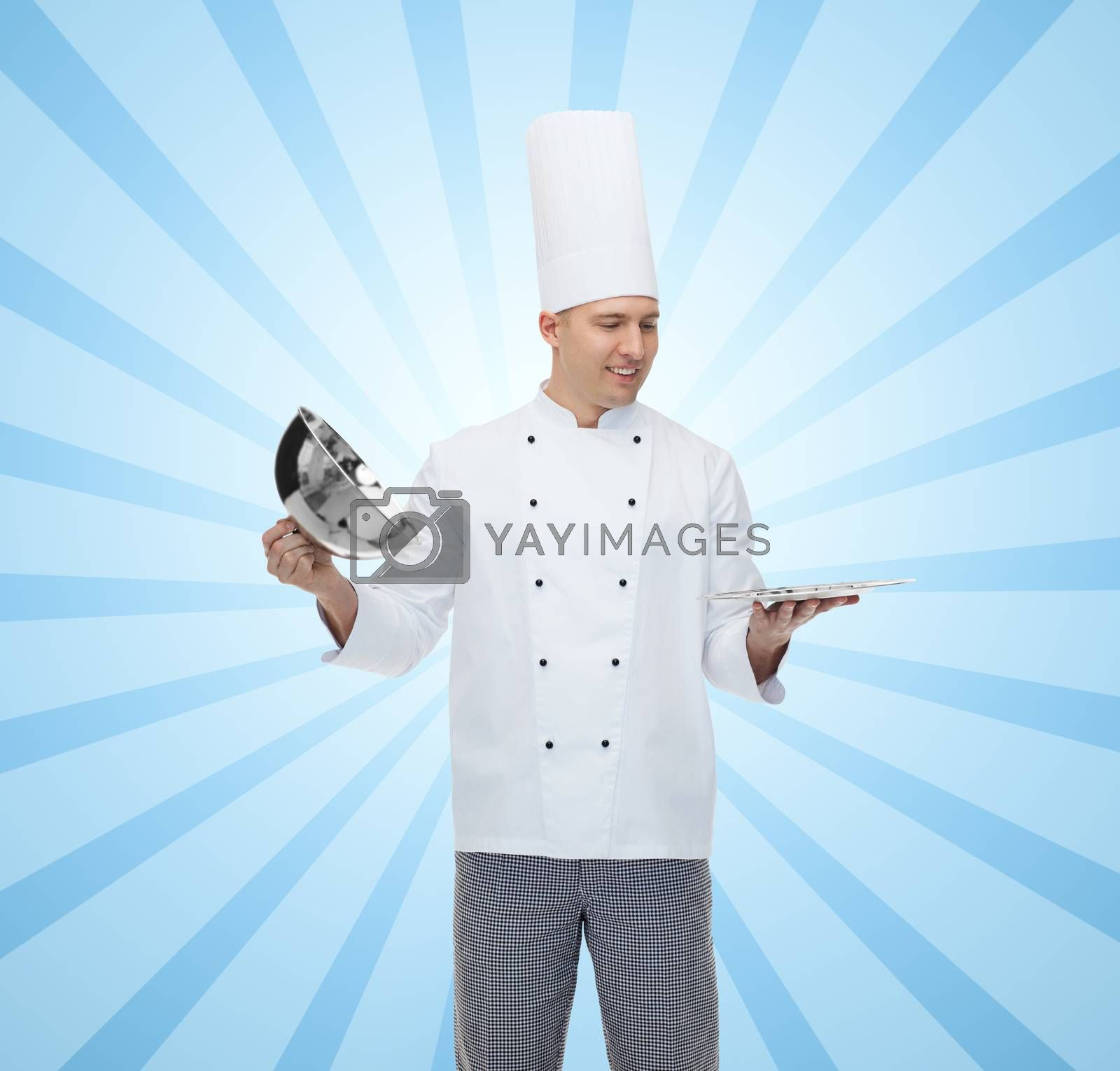 cooking, profession and people concept - happy male chef cook opening cloche cover over blue burst rays background