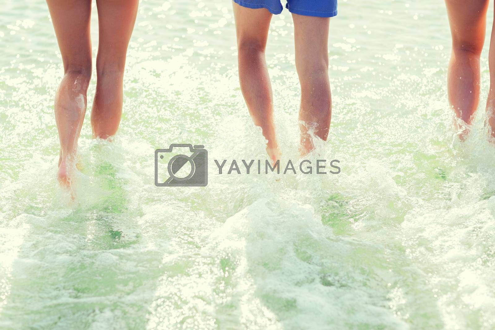 sea, summer vacation, holidays and people concept - close up of human legs walking on summer beach