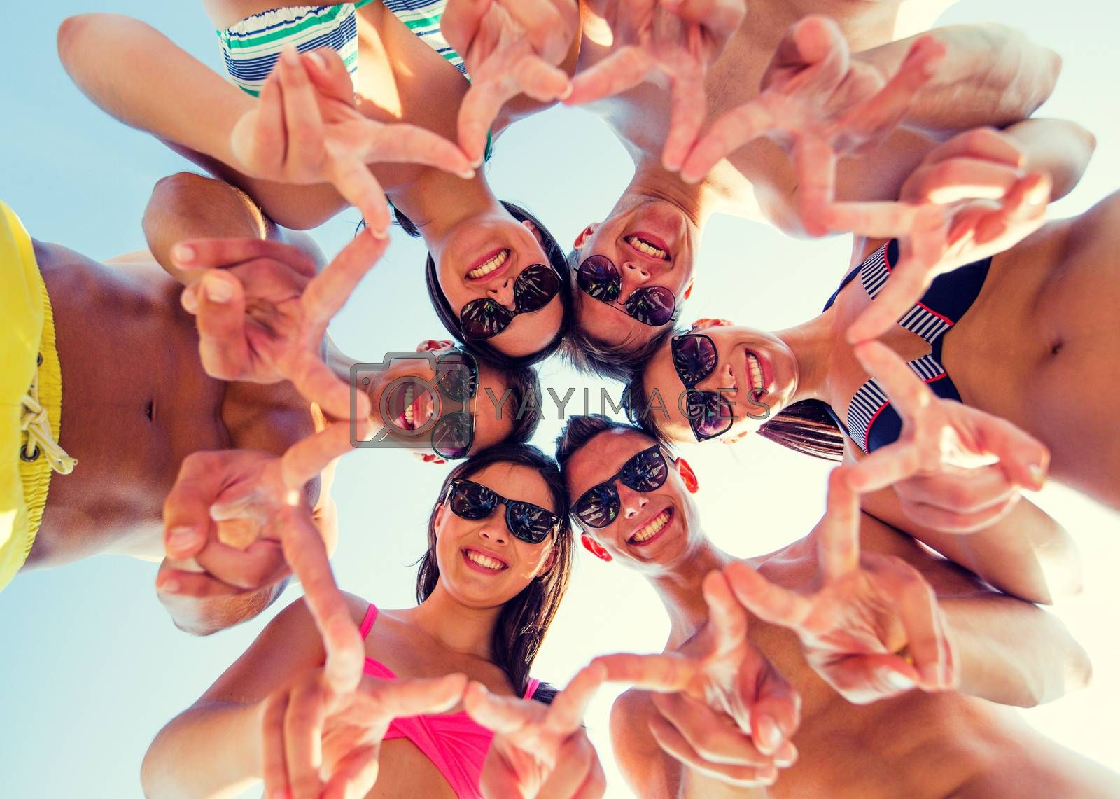 friendship, happiness, summer vacation, holidays and people concept - group of smiling friends wearing swimwear and showing victory or peace sign standing in circle over blue sky