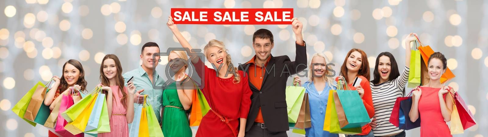 consumerism, people and discount concept - group of happy people with sale sign and shopping bags over holidays lights background