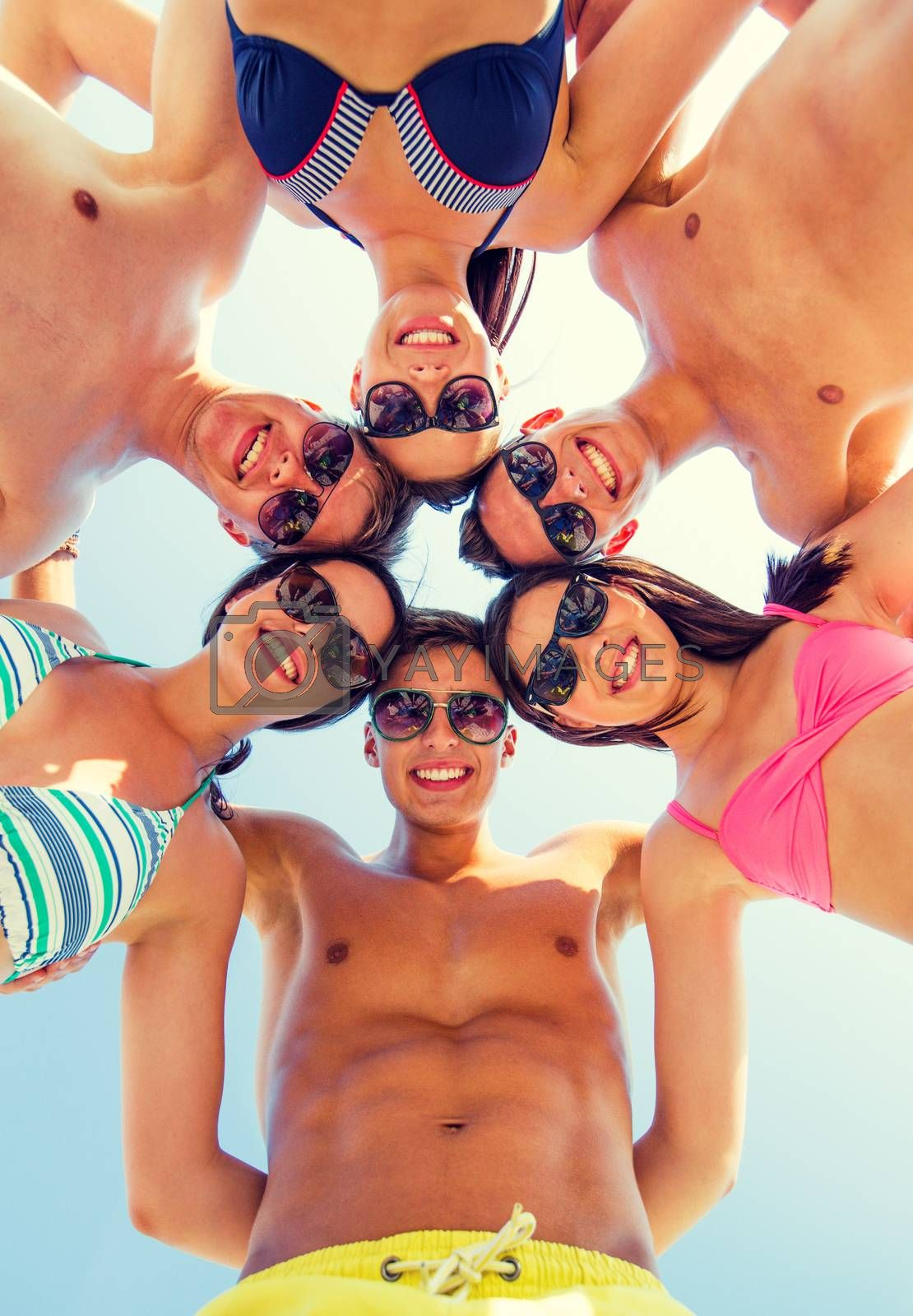 friendship, happiness, summer vacation, holidays and people concept - group of smiling friends wearing swimwear standing in circle over blue sky