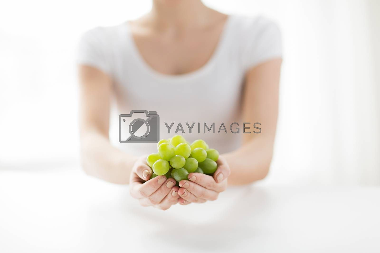healthy eating, dieting, vegetarian food and people concept - close up of woman hands holding green grape bunch at home