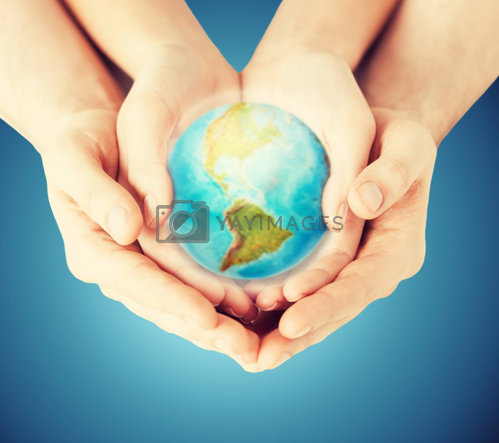 Royalty free image of close up of woman and man hands with earth globe by dolgachov