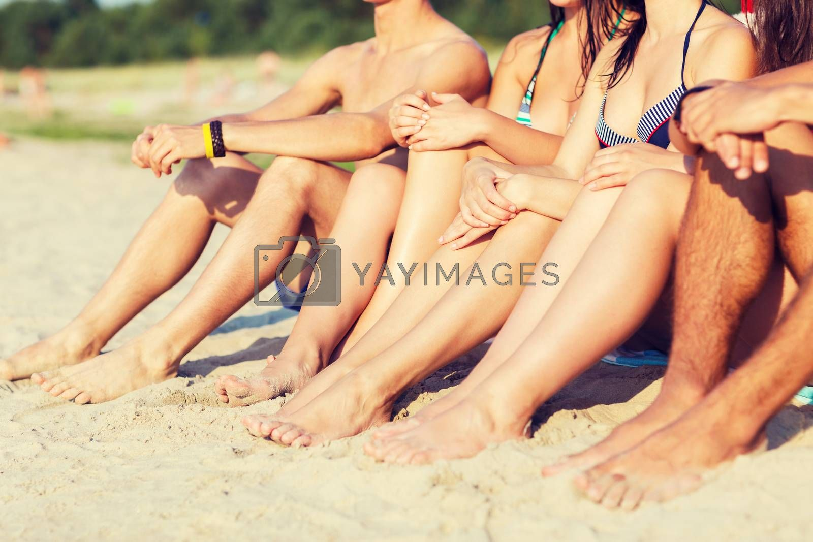 Royalty free image of close up of friends sitting on summer beach by dolgachov