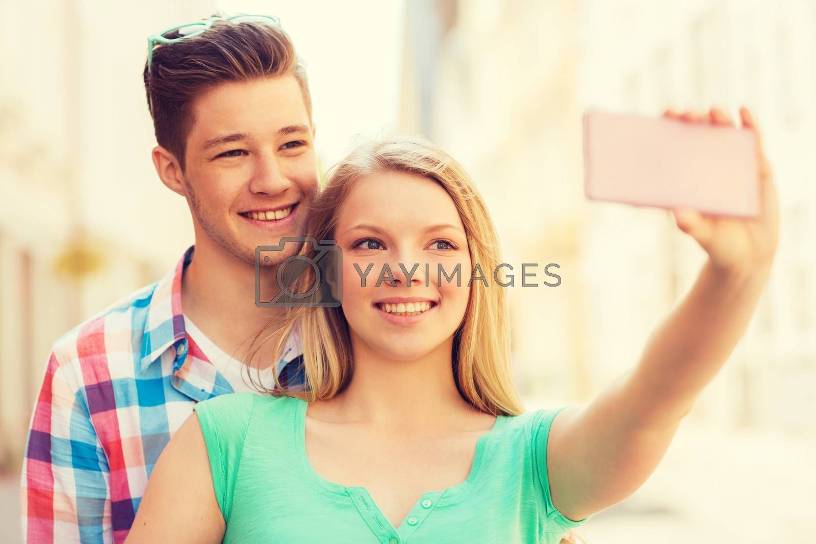 Royalty free image of smiling couple with smartphone in city by dolgachov