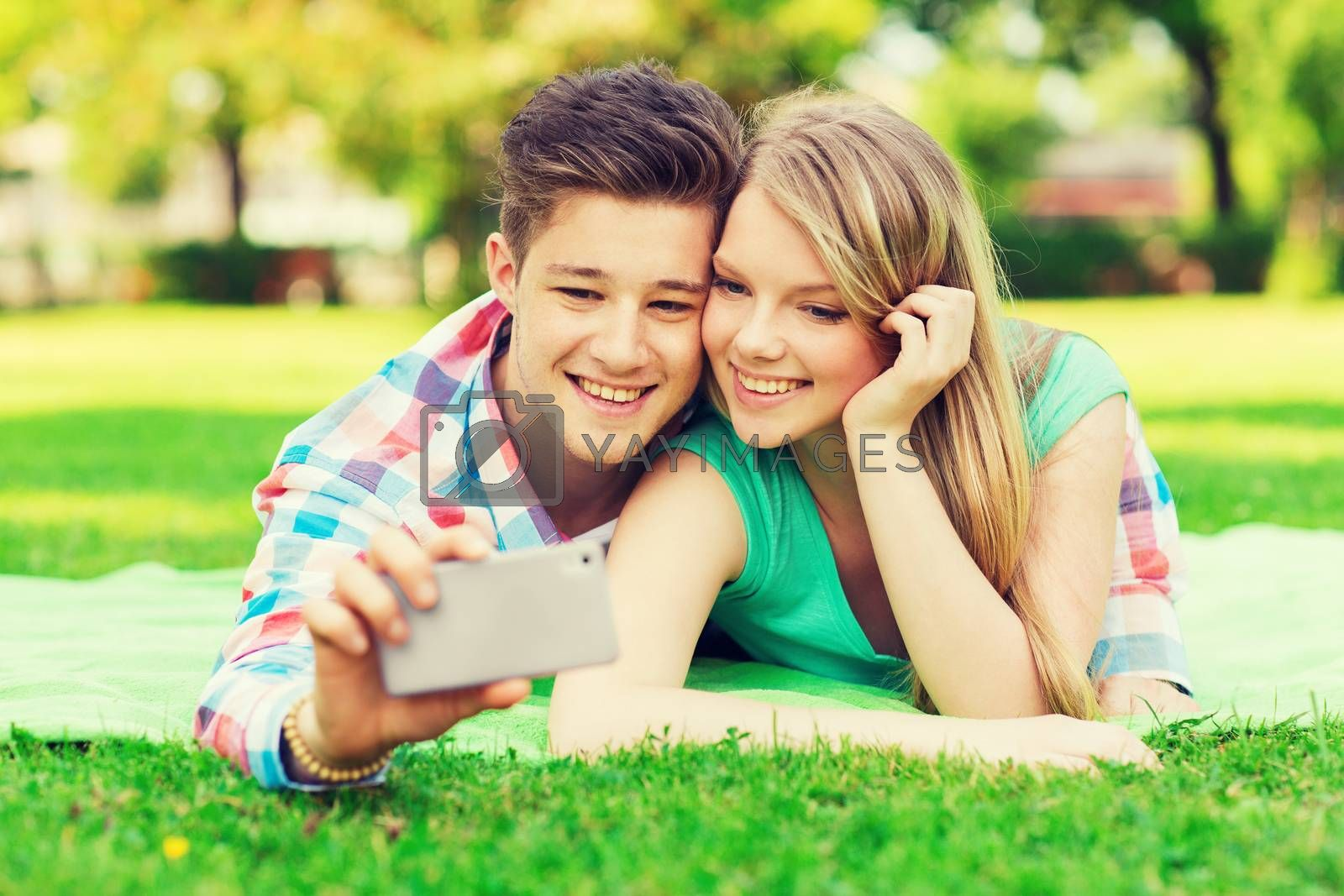 vacation, holidays, technology and friendship concept - smiling couple lying on blanket and making selfie with smartphone in park
