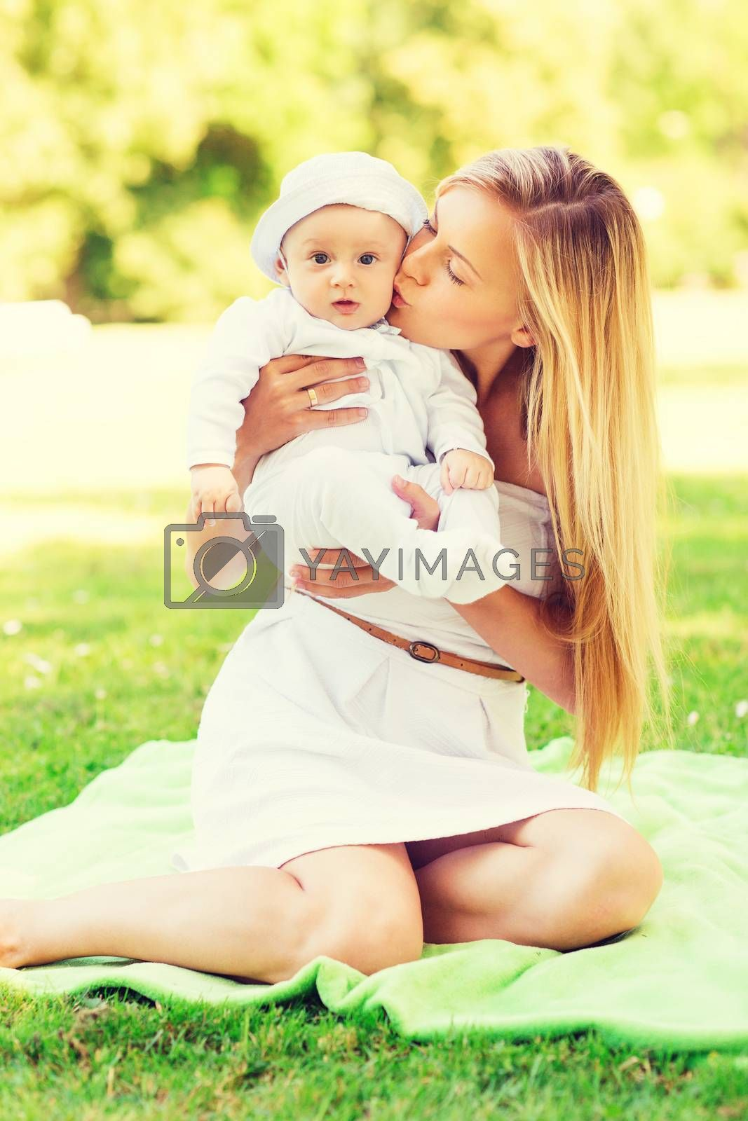 Royalty free image of happy mother with little baby sitting on blanket by dolgachov