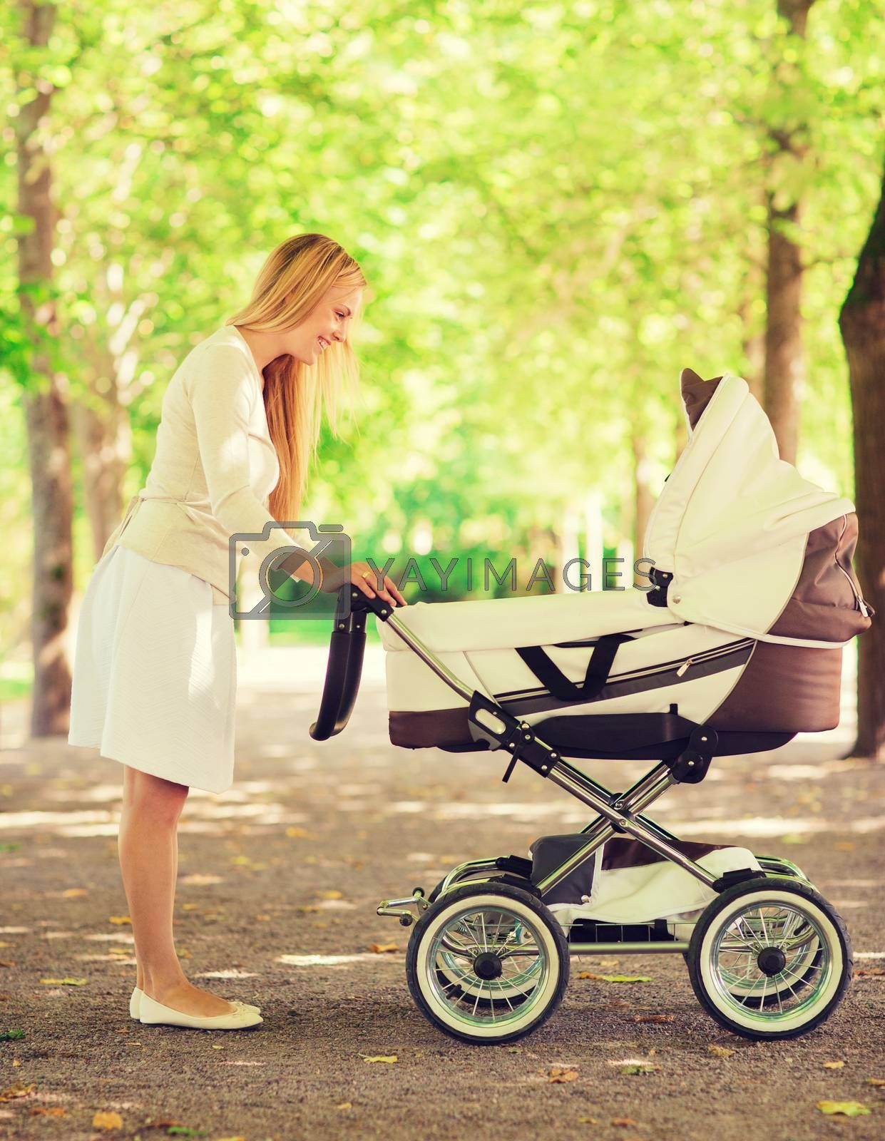 Royalty free image of happy mother with stroller in park by dolgachov