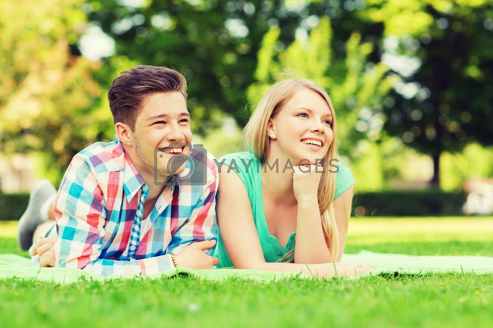 Royalty free image of smiling couple lying on blanket in park by dolgachov