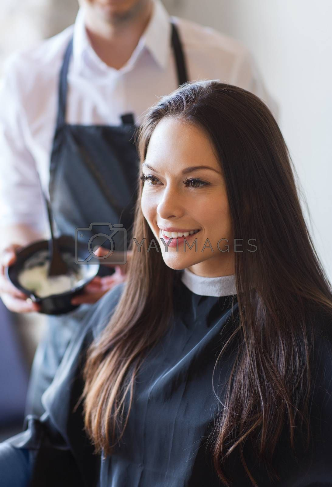 Royalty free image of happy young woman coloring hair at salon by dolgachov
