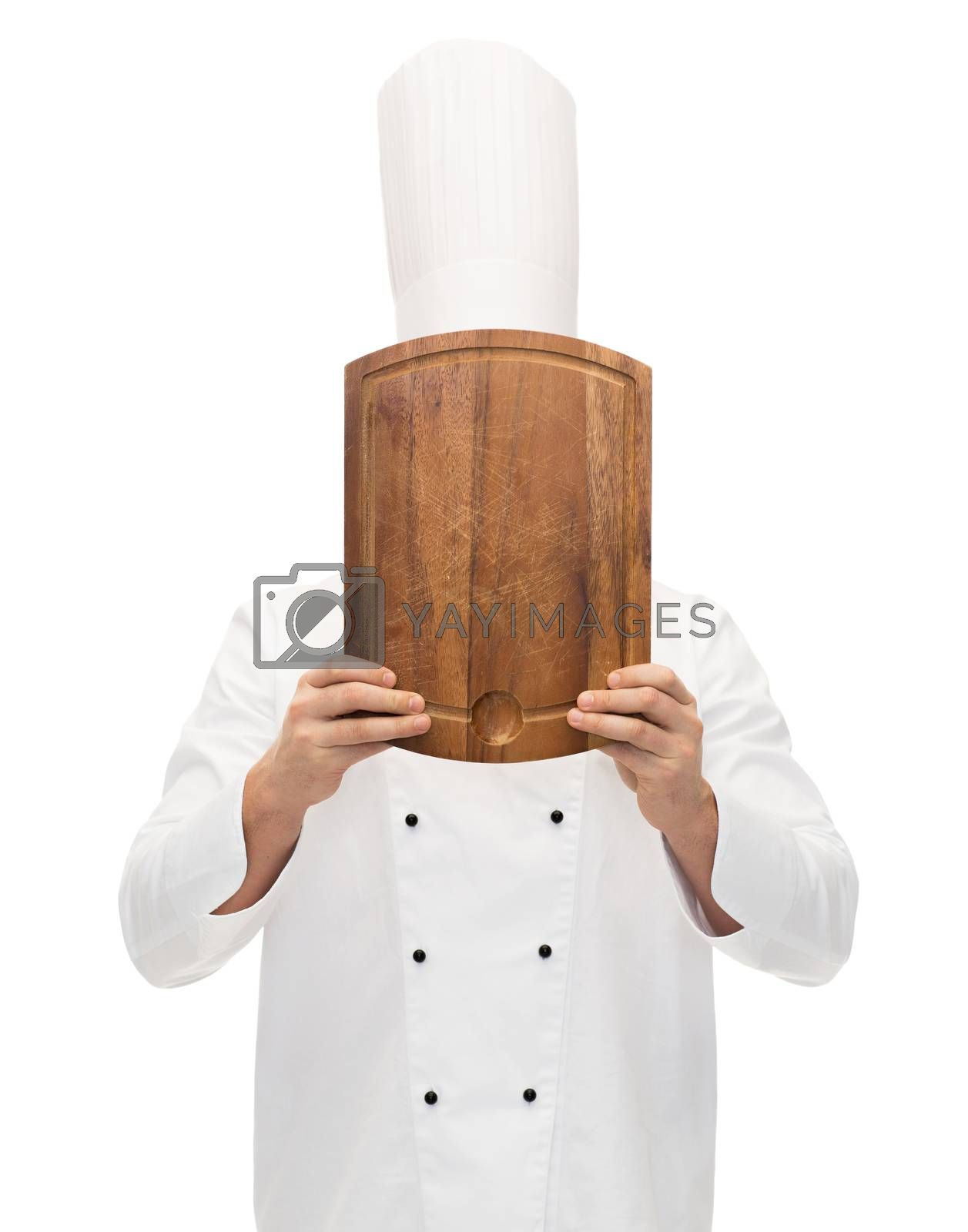 Royalty free image of male chef cook covering face with cutting board by dolgachov