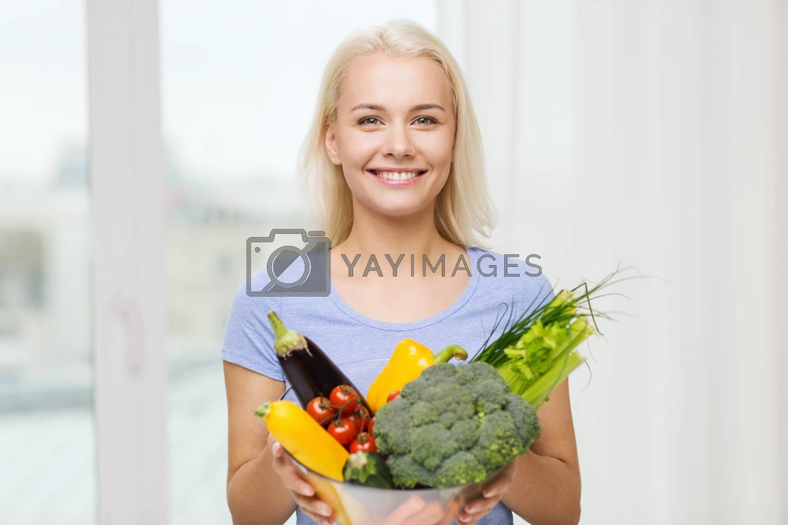 Royalty free image of smiling young woman with vegetables at home by dolgachov