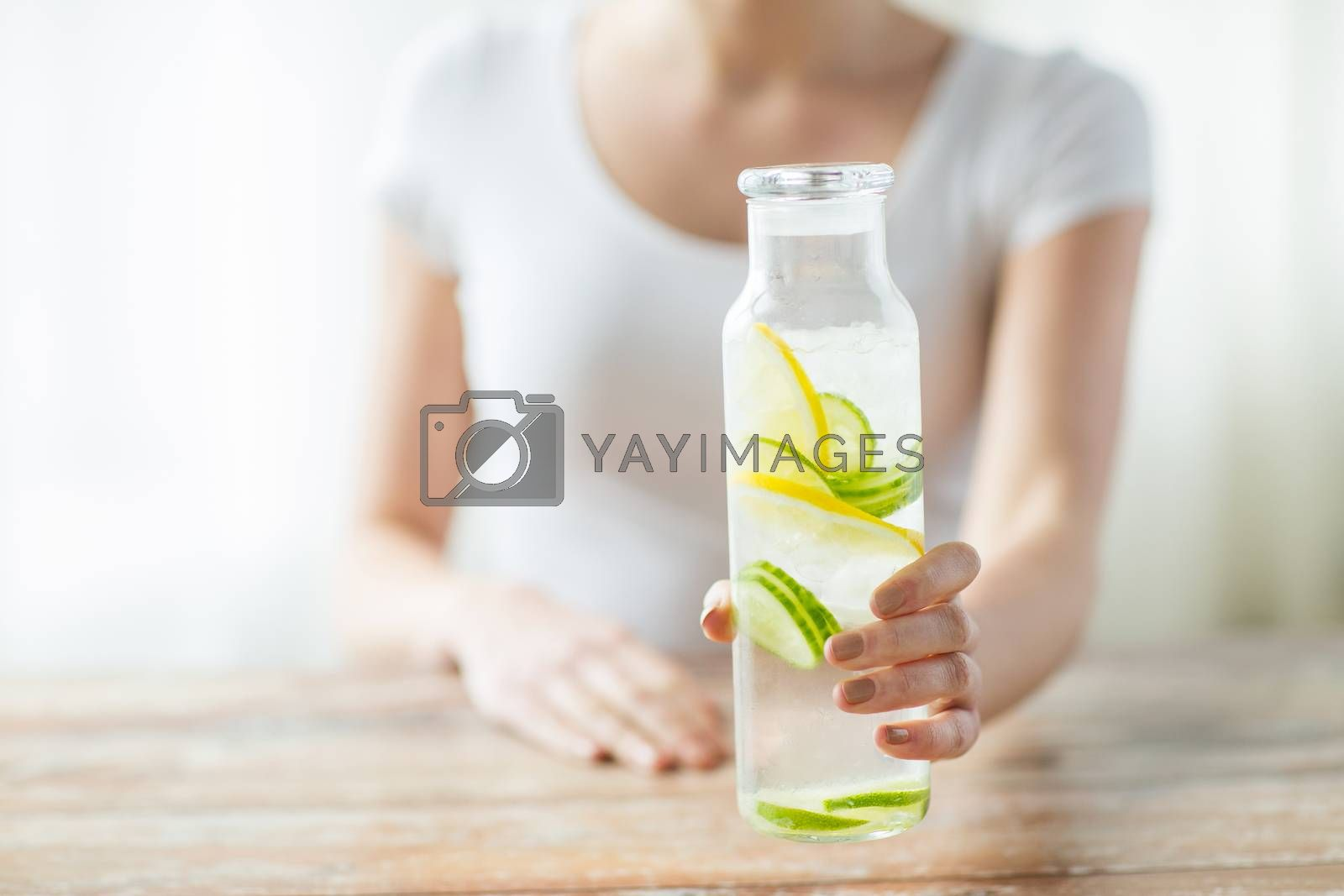 Royalty free image of close up of woman with fruit water in glass bottle by dolgachov