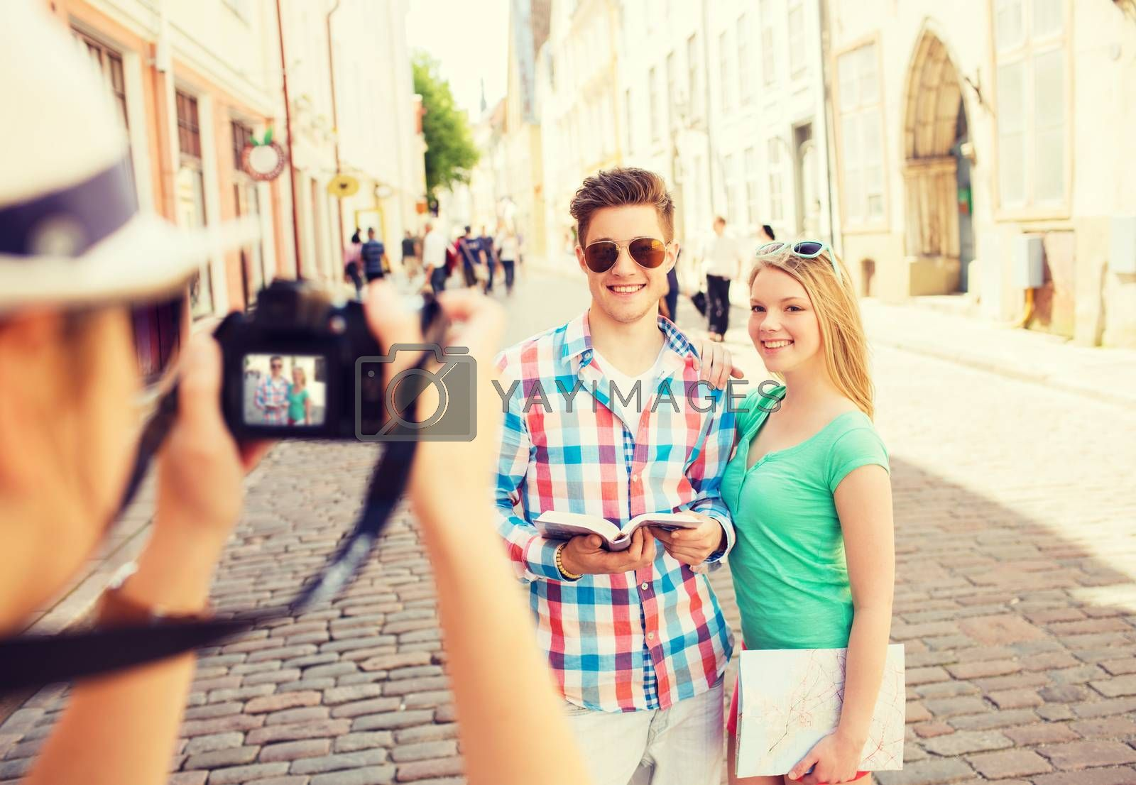 Royalty free image of smiling couple with map and photo camera in city by dolgachov