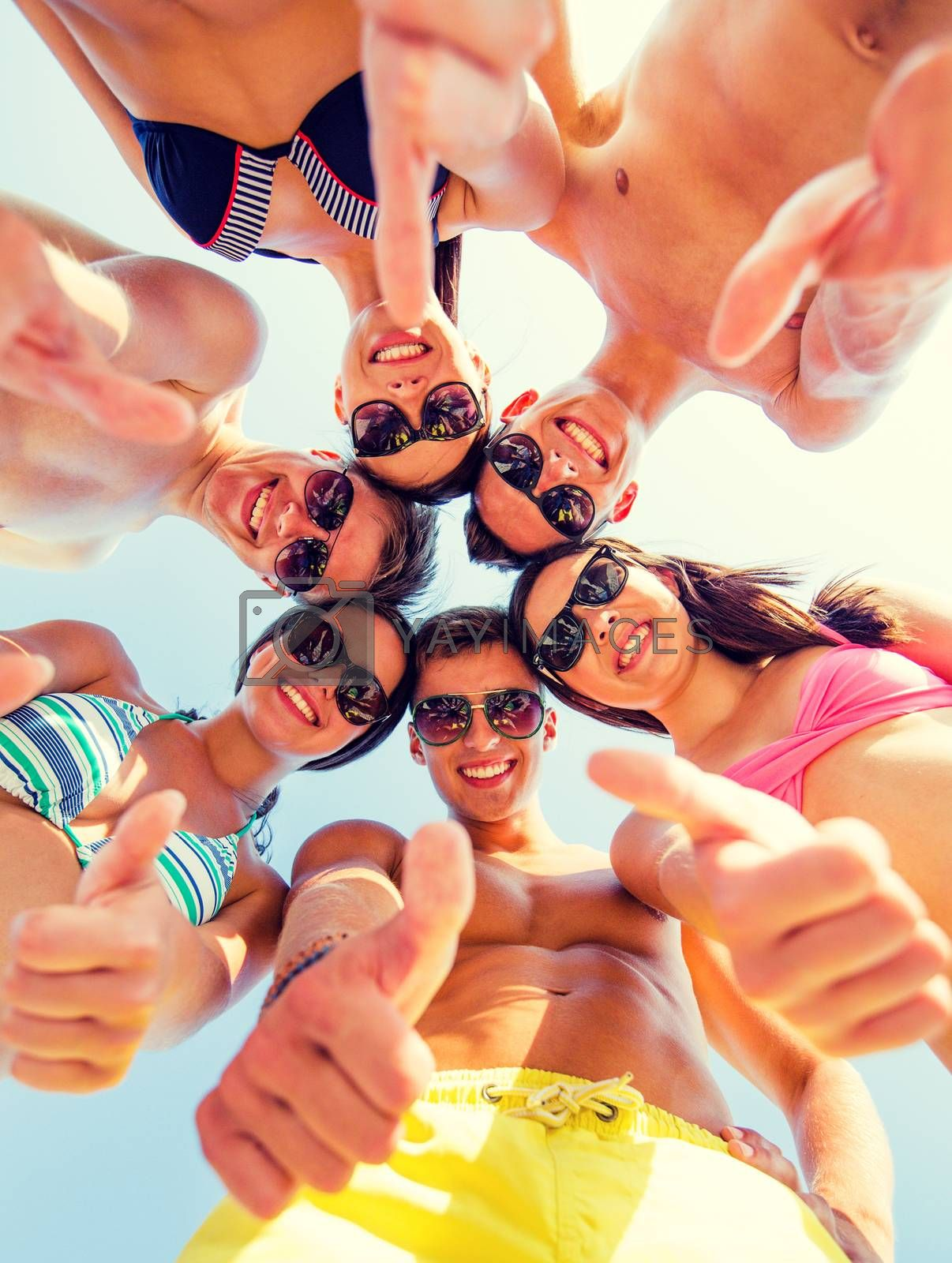 Royalty free image of smiling friends showing thumbs up in circle by dolgachov