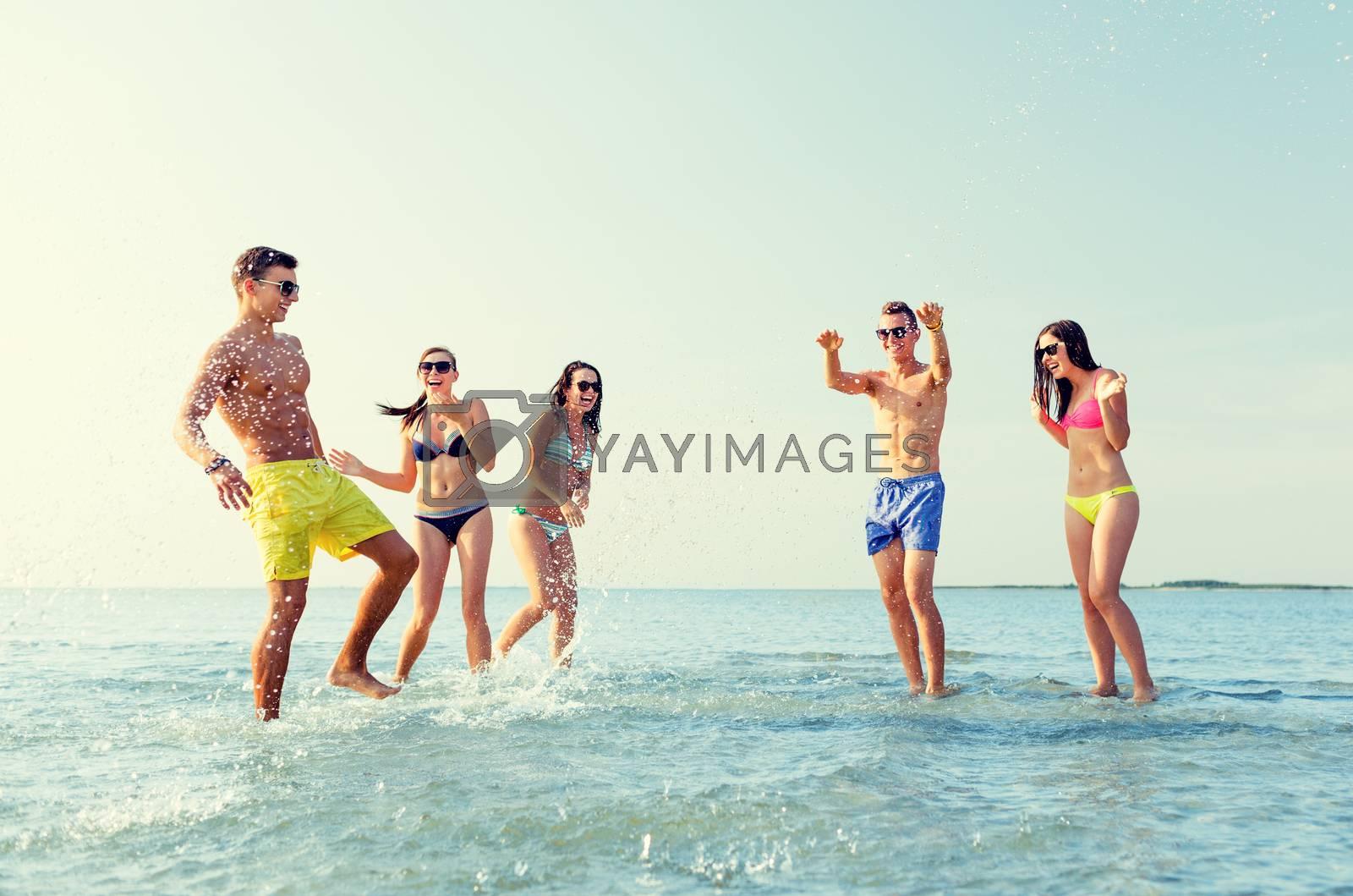 Royalty free image of happy friends having fun on summer beach by dolgachov
