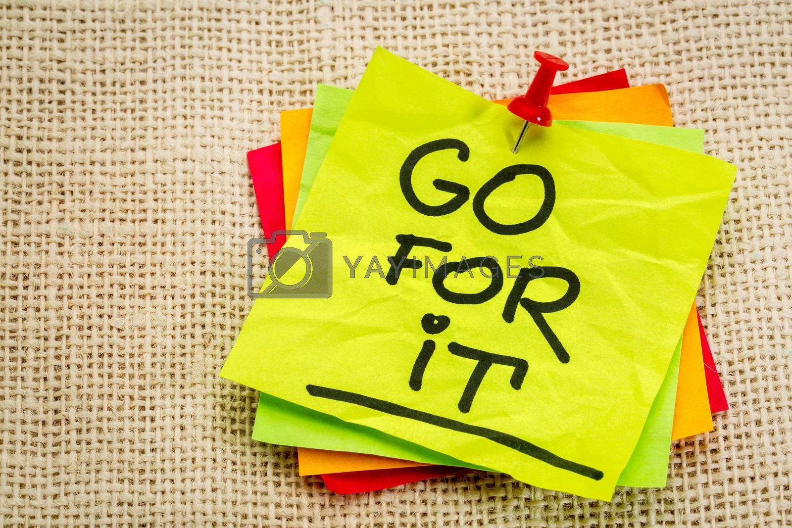 Go for it - motivational handwriting on a sticky note against burlap canvas